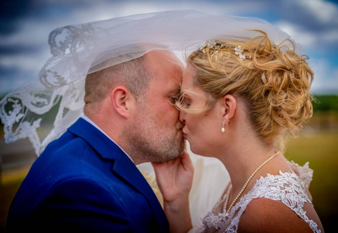 YFFUK Phil Endicott Flinders Whittlebury Hall Northamptonshire newly married couple kissing outside with the veil blowing over them