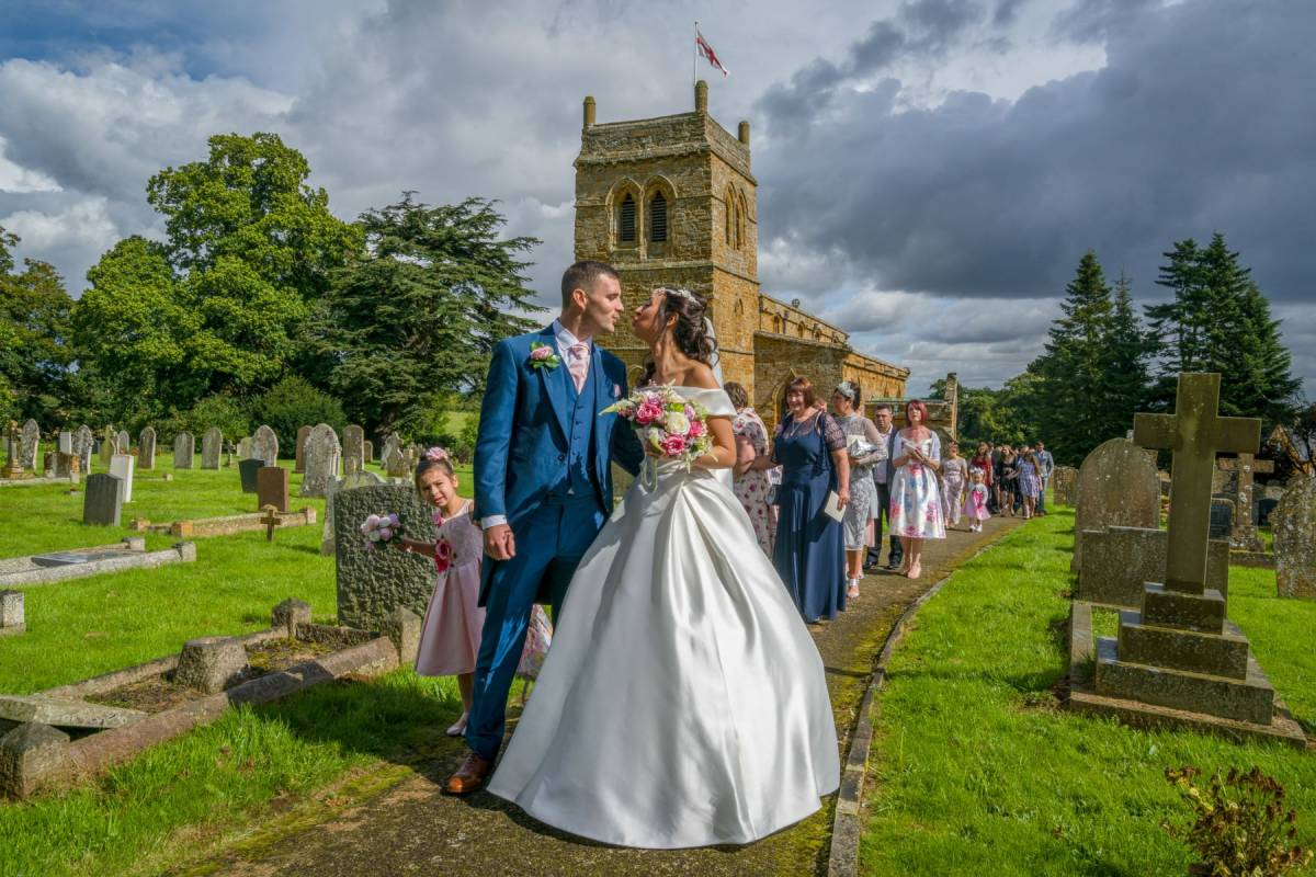 YFFUK Phil Endicott Gorman St Andrews Church Harlestone Northamptonshire couple outside their church newly married about to kiss