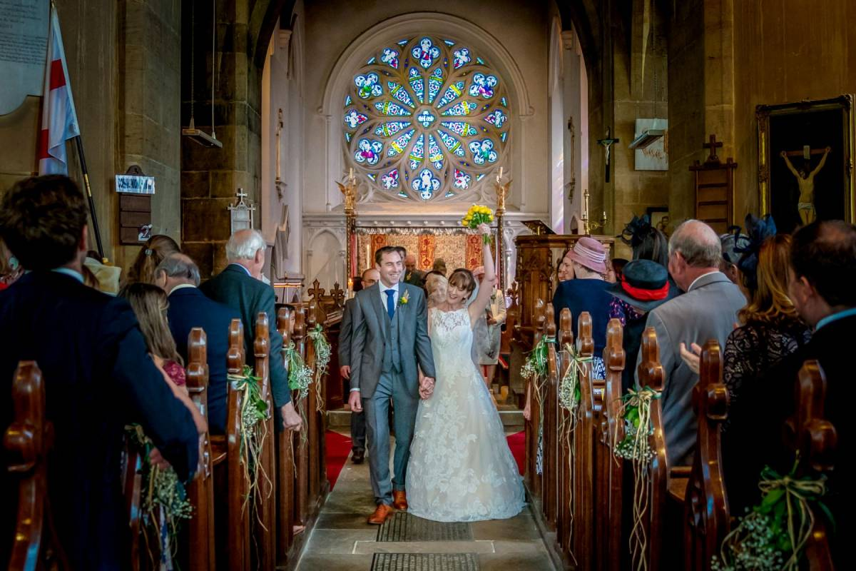 YFFUK Phil Endicott Tarry St Marys Church Orlingbury Northamptonshire bride holds her flowers high above her leaving church newly married