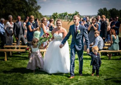 YFFUK Phil Endicott Hasseldine Elms Meadow Tipi Wedding Venue Kettering Northamptonshire couple walking the aisle after their vows with their children