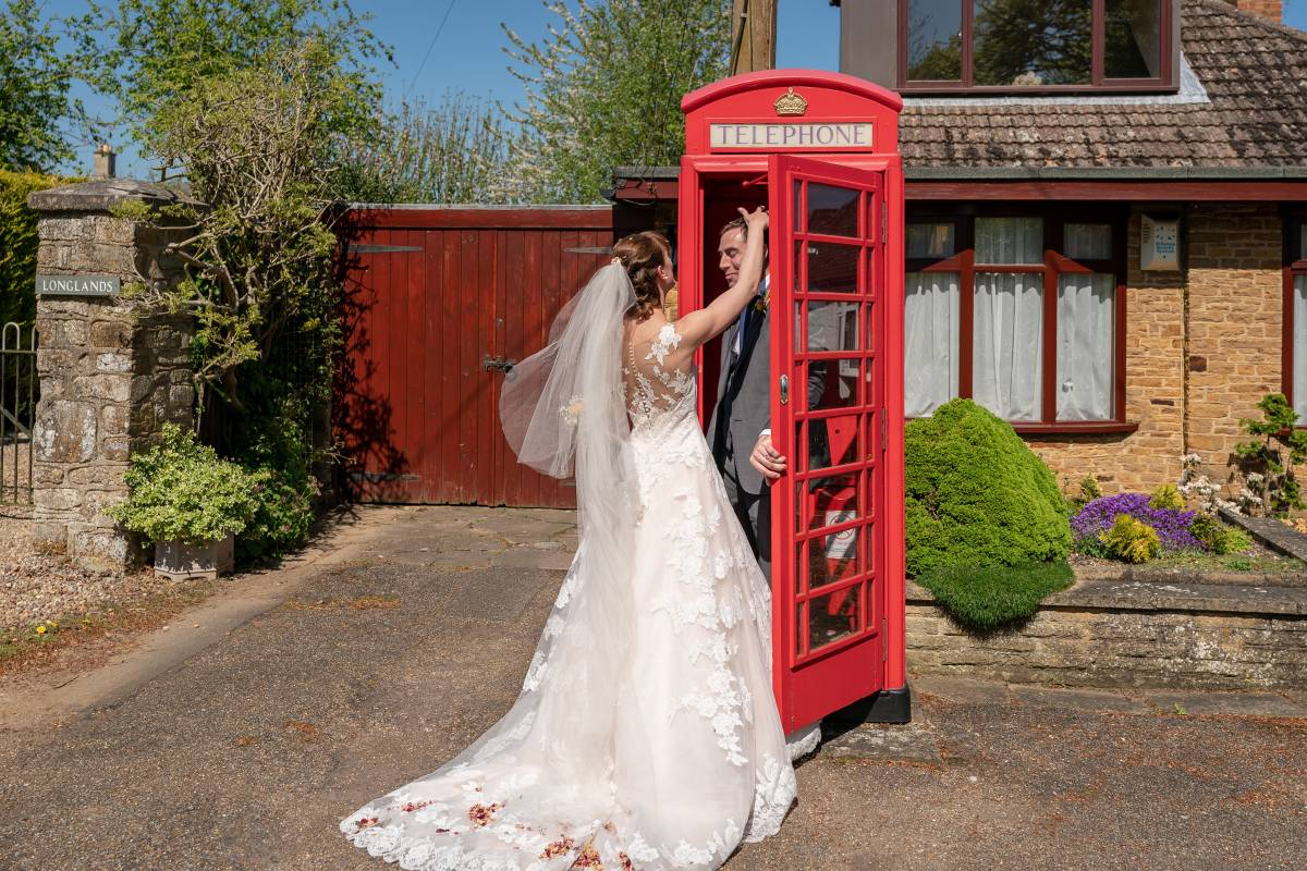 YFFUK Phil Endicott Tarry St Marys Church Orlingbury Northamptonshire bride by a red telephone box groom is inside