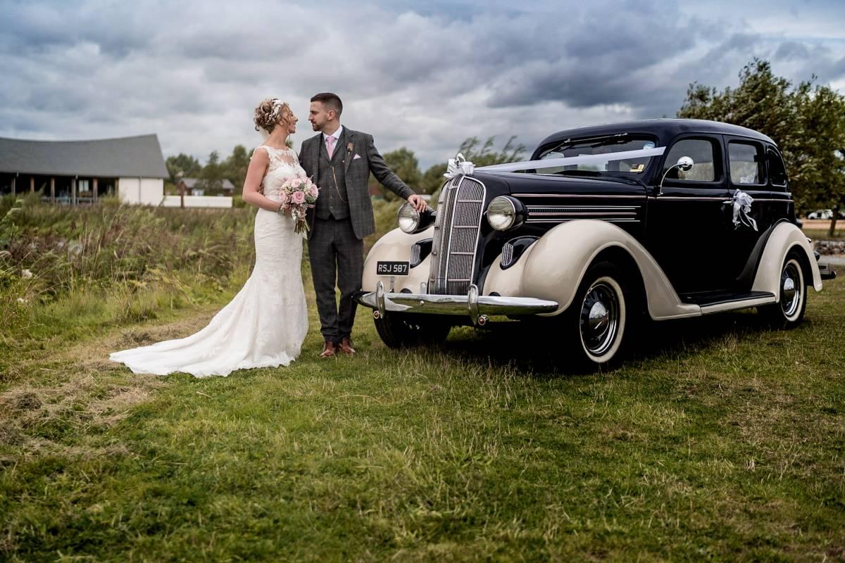 YFFUK Phil Endicott Smith Bonham Stanwick Hotel Courtyard Northamptonshire newly married couple with their dads wedding car
