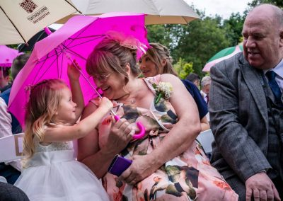 YFFUK Phil Endicott Smith Bonham Stanwick Hotel Courtyard Stanwick Northamptonshire daughter of bride and groom under an pink small umbrella with her grandmother