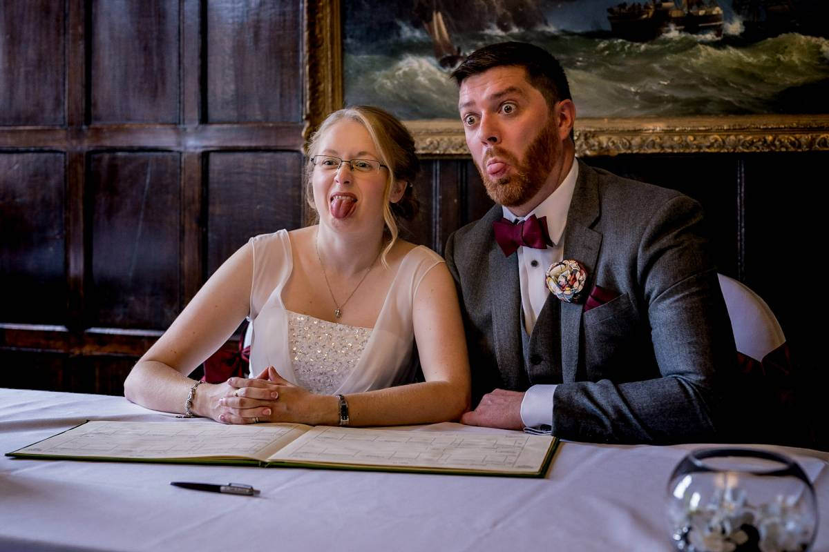 Talbot Hotel Oundle bride and groom signing wedding register groom sticking his tongue out bride pulling funny face
