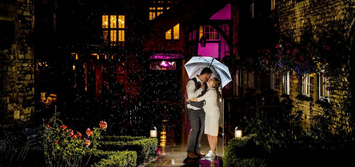 yffuk newly married couple under an umbrella in the pink lit rain talbot hotel oundle