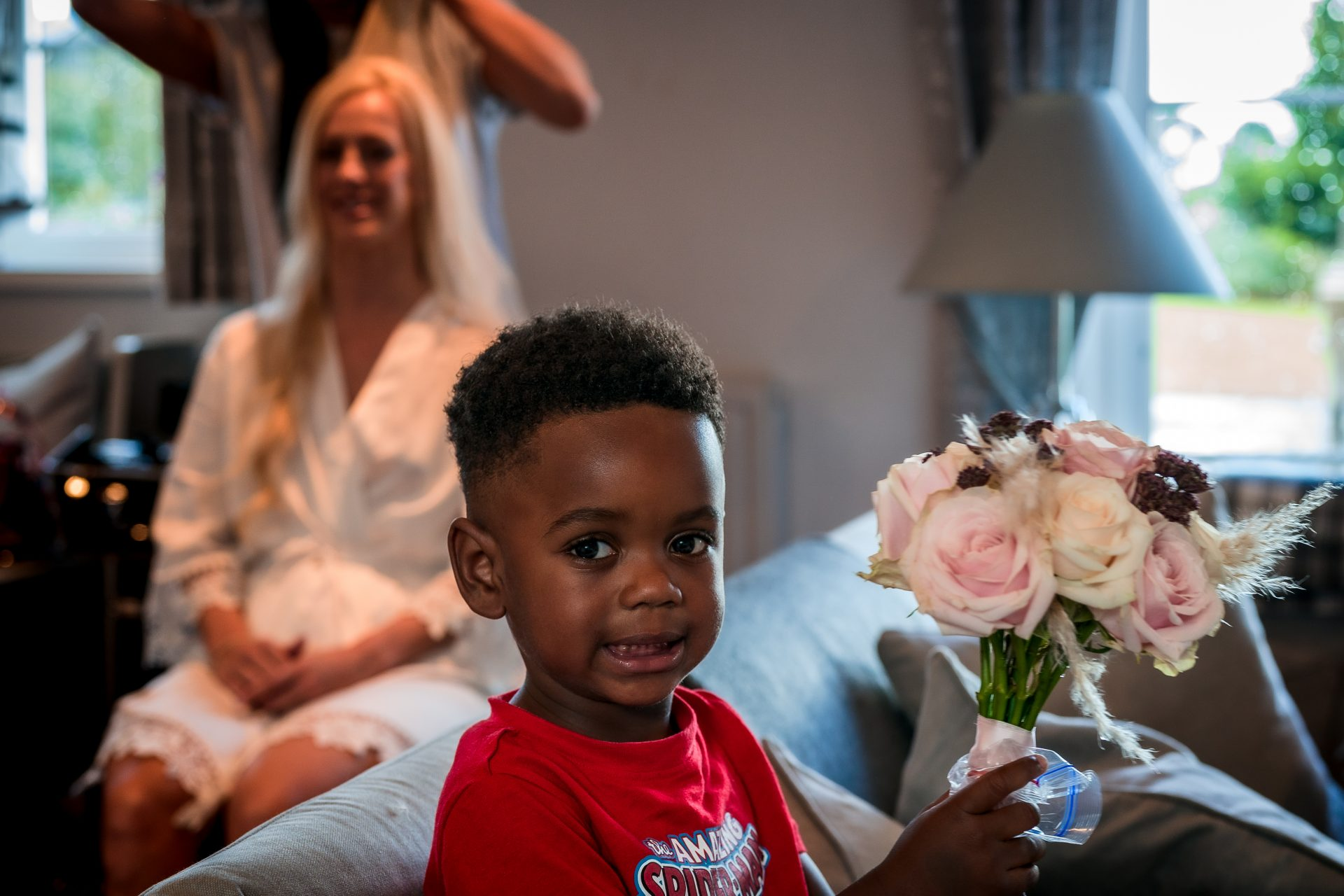 YFFUK Mwasuku Phil Endicott Page Boy holding the bridal bouquet as she has her hair styled