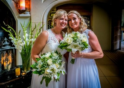 YFFUK Phil Endicott Davies Delapre Abbey Northampton LGBT brides holding their bouquets after their wedding ceremony