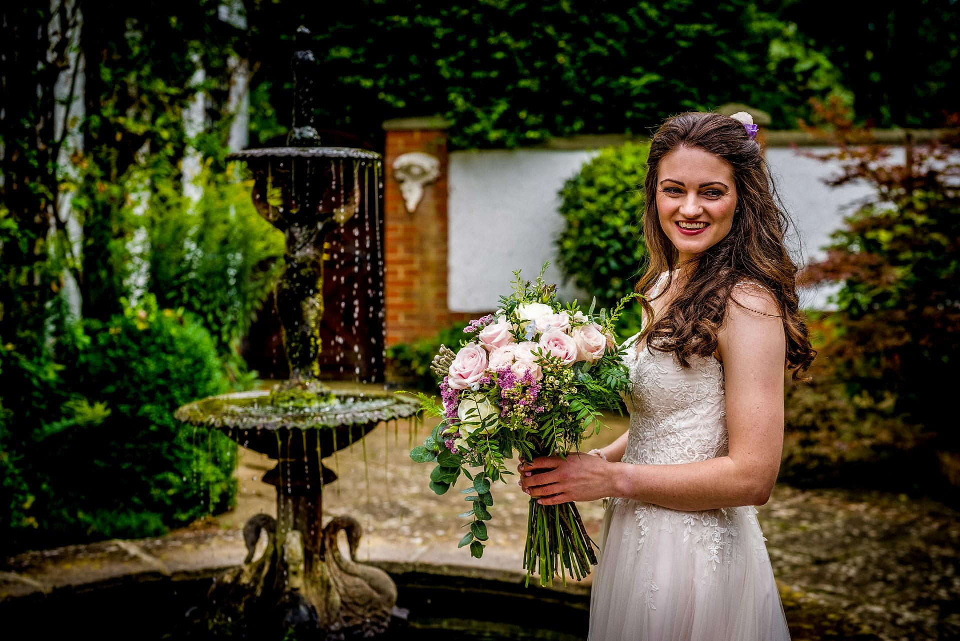 YFFUK Phil Endicott Johnson Stanwick Hotel Courtyard Northamptonshire bride showing her bouquet by the water fountain