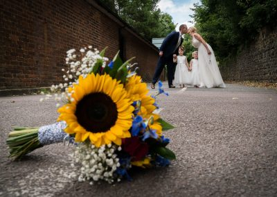YFFUK Phil Endicott Murray Best Western Moore Place Hotel Aspley Guise married couple kissing with daughters between them with bridal bouquet of sunflowers in foreground