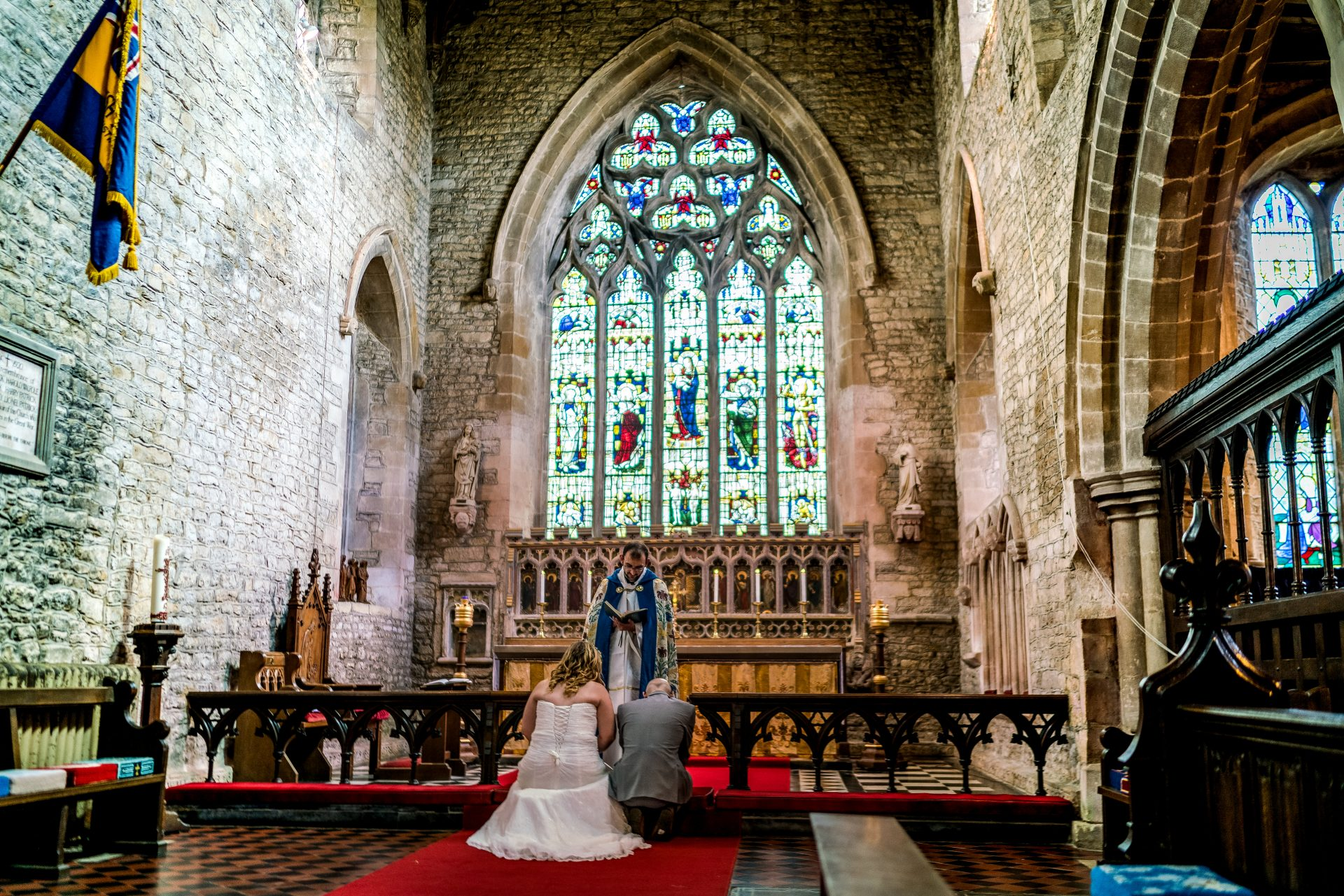 YFFUK Phil Endicott Zilka Geddington St Mary Magdalene Church Northants groom bride knelling at the church font