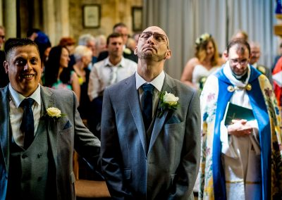 YFFUK Phil Endicott Zilka Geddington St Mary Magdalene Church Northants groom getting nervous before his wedding bride in background walking the aisle