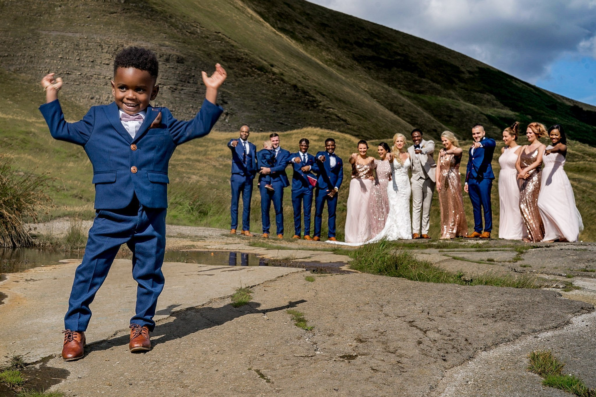YFFUK Your Favourite Frame Mwasuku Peak District Castleton Mam Tor Bridal Party pointing at the page boy who is dancing close to the camera