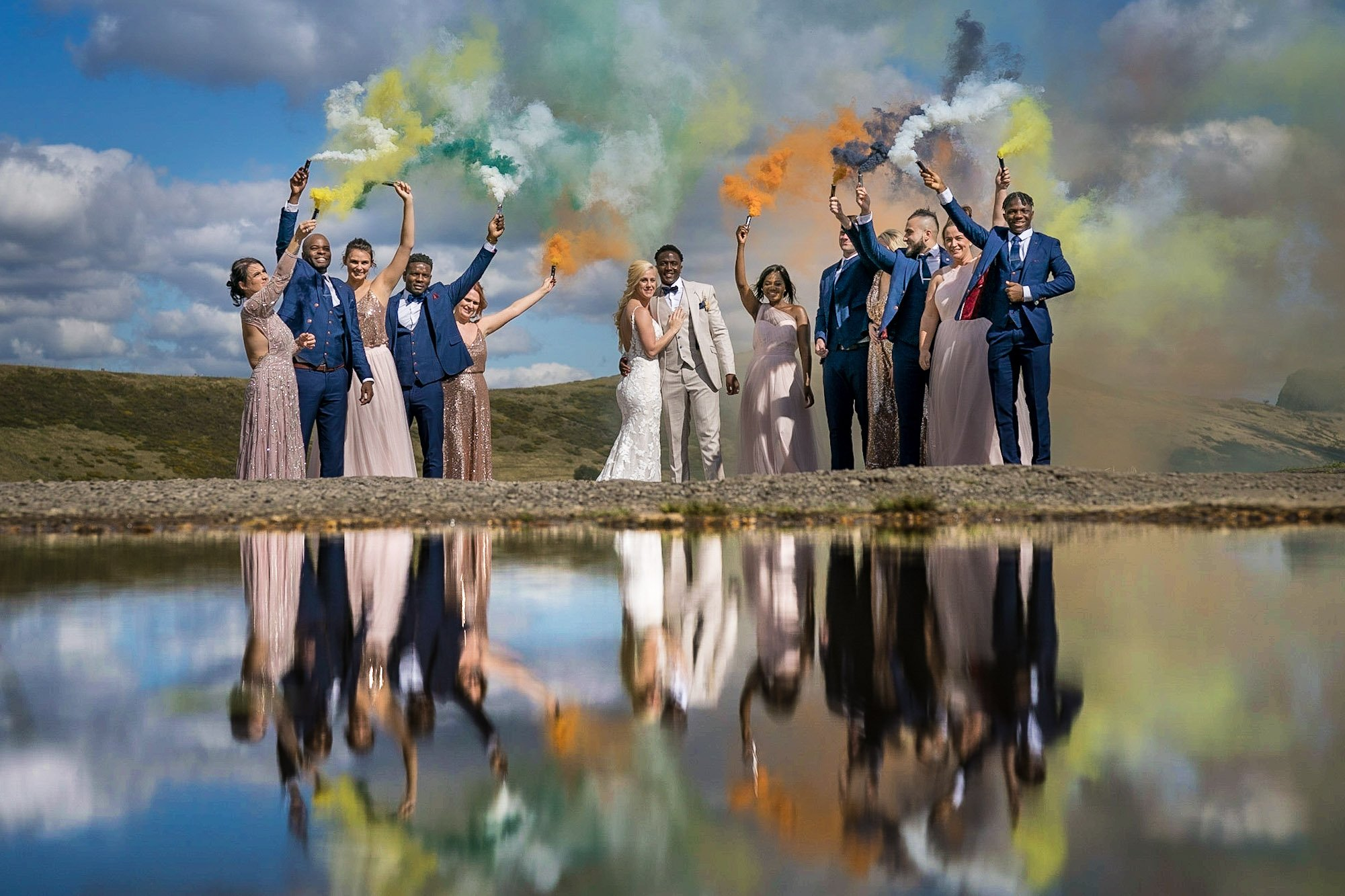 YFFUK Your Favourite Frame Mwasuku Peak District Castleton Mam Tor Bridal party reflected in the water pool in the old road holding smoke bombs grenades of different colours