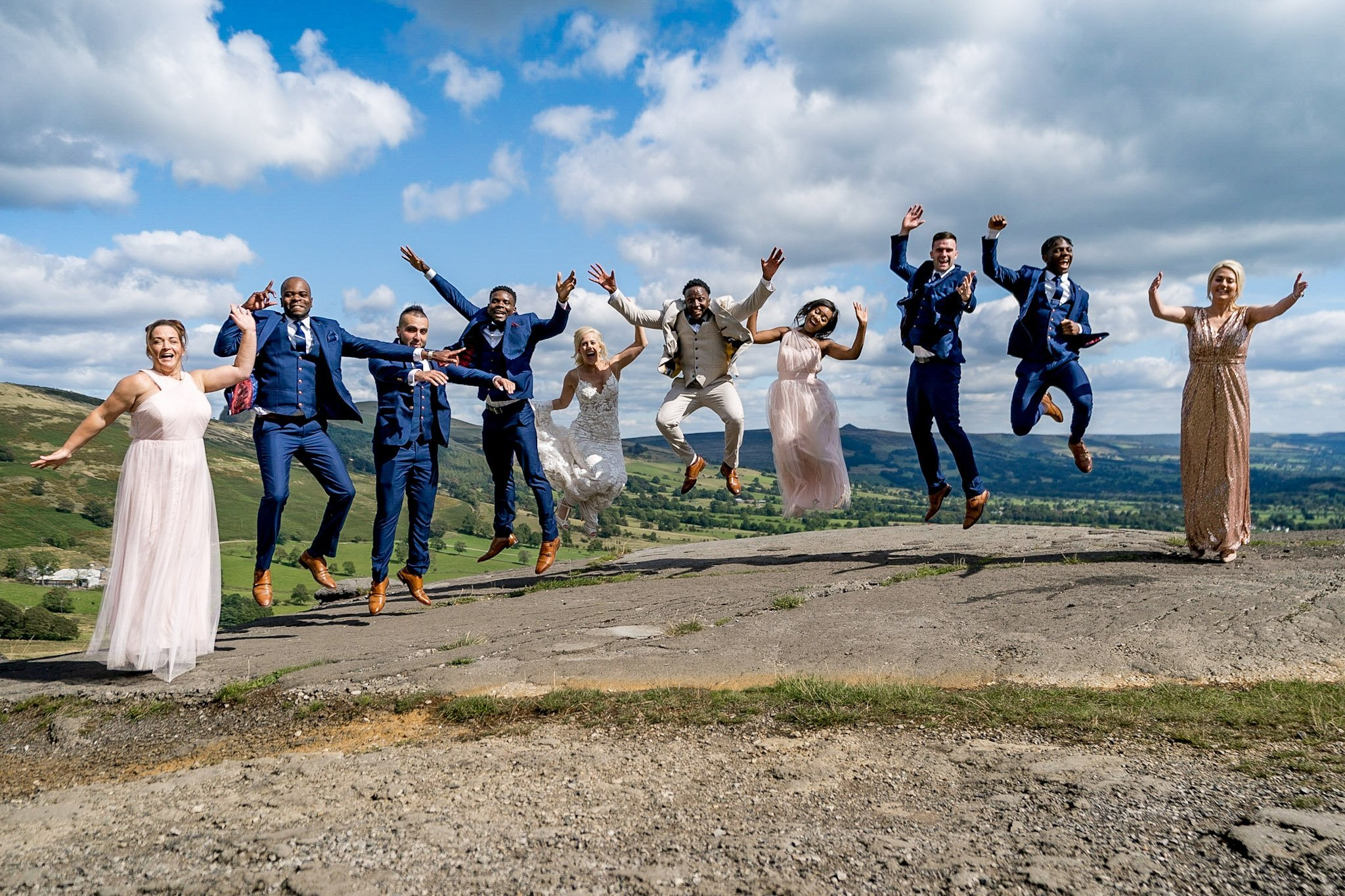 YFFUK Your Favourite Frame Mwasuku Peak District Castleton Mam Tor bride and groom doing star jumps with their bridal party in the peaks with a gorgeous background setting