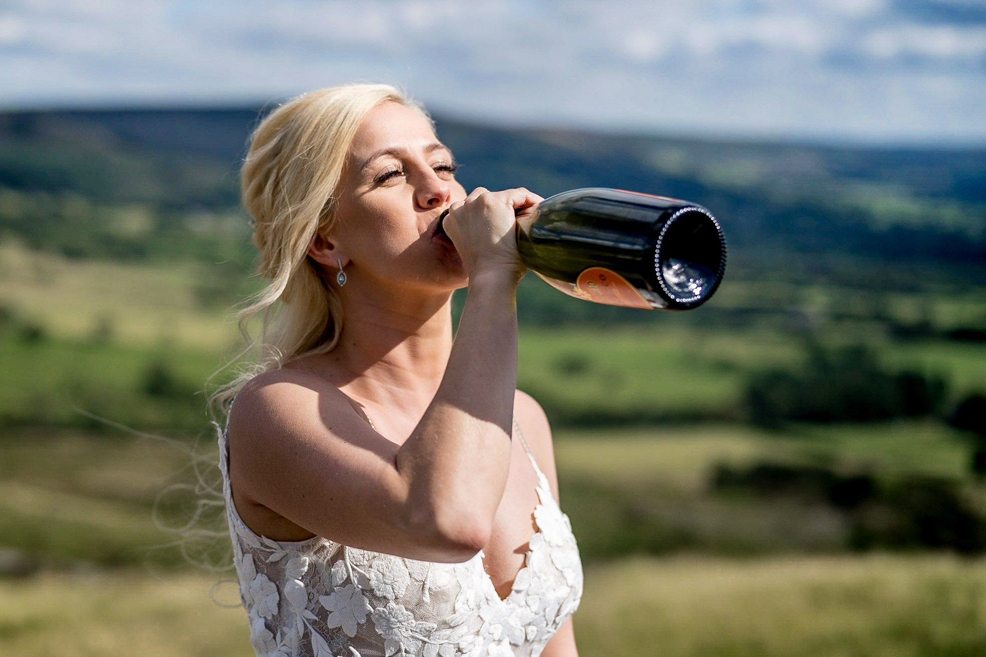 YFFUK Your Favourite Frame Mwasuku Peak District Castleton Mam Tor bride drinking from the champagne bottle celebrating the happiness