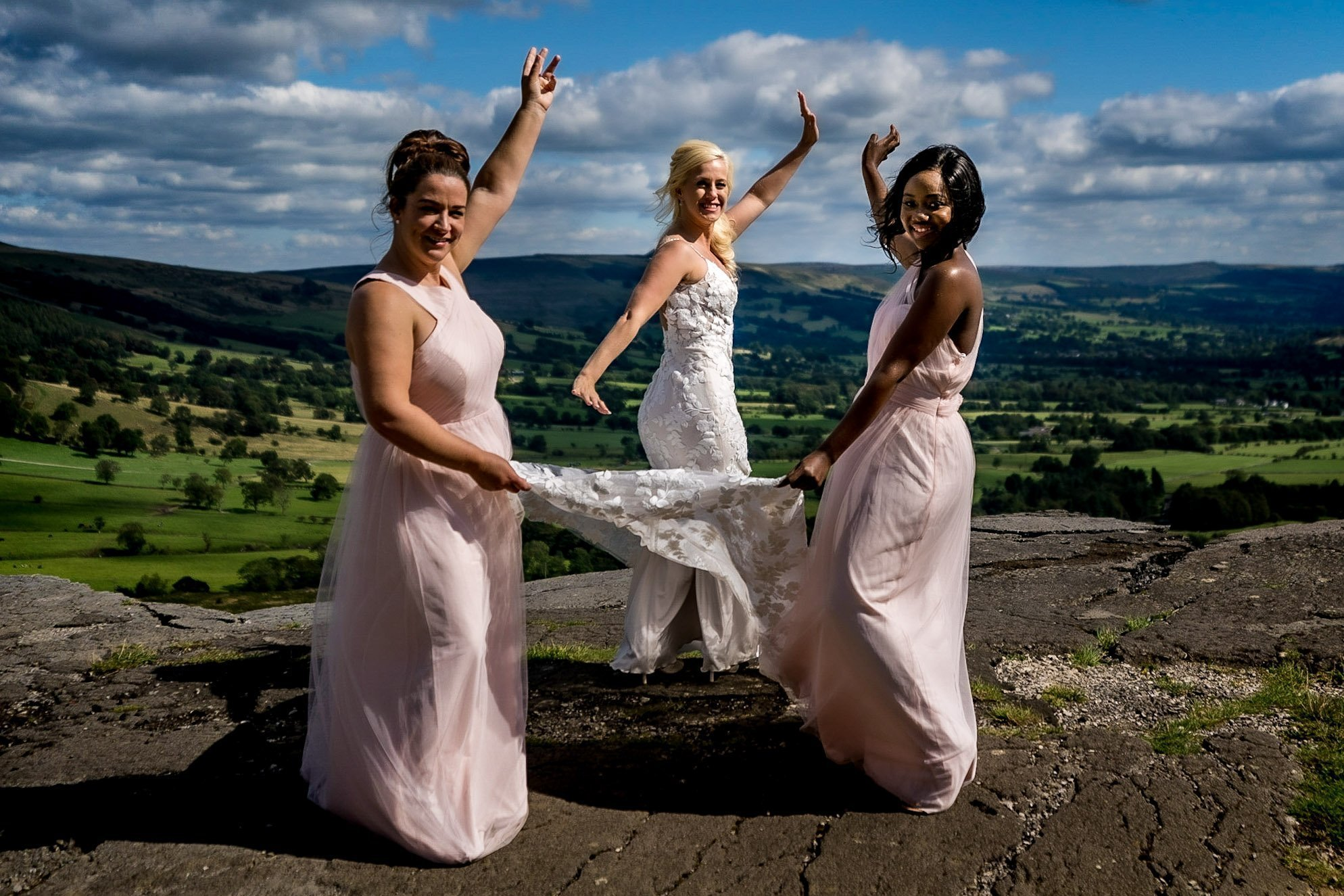 YFFUK Your Favourite Frame Mwasuku Peak District Castleton Mam Tor bride standing on the old cracked road with her bridesmaids holding the train of her dress blue skies and killer views
