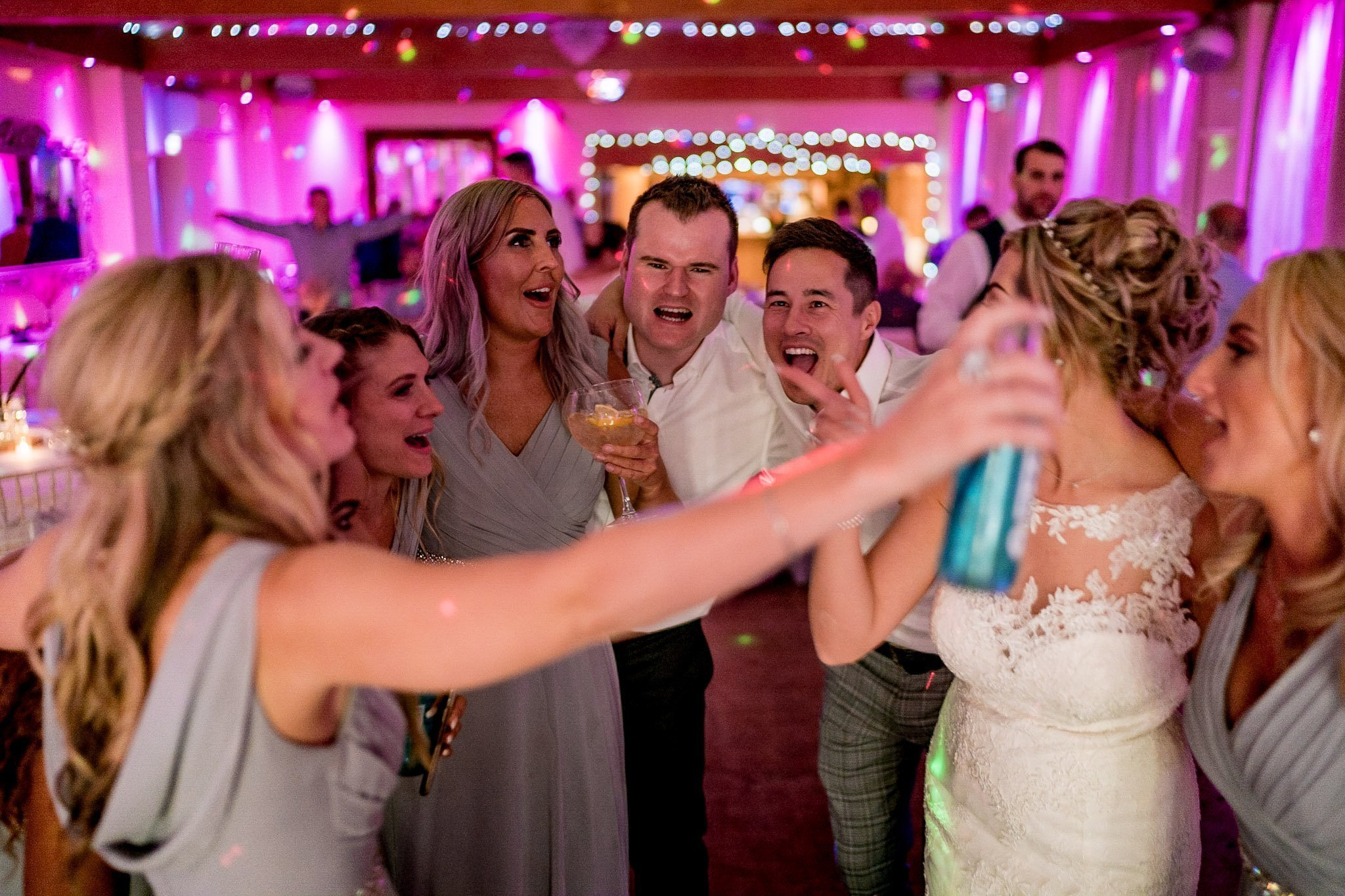 YFFUK Your Favourite Frame Stanwick Hotel bridal party huddle on the dancefloor Reflections Suite