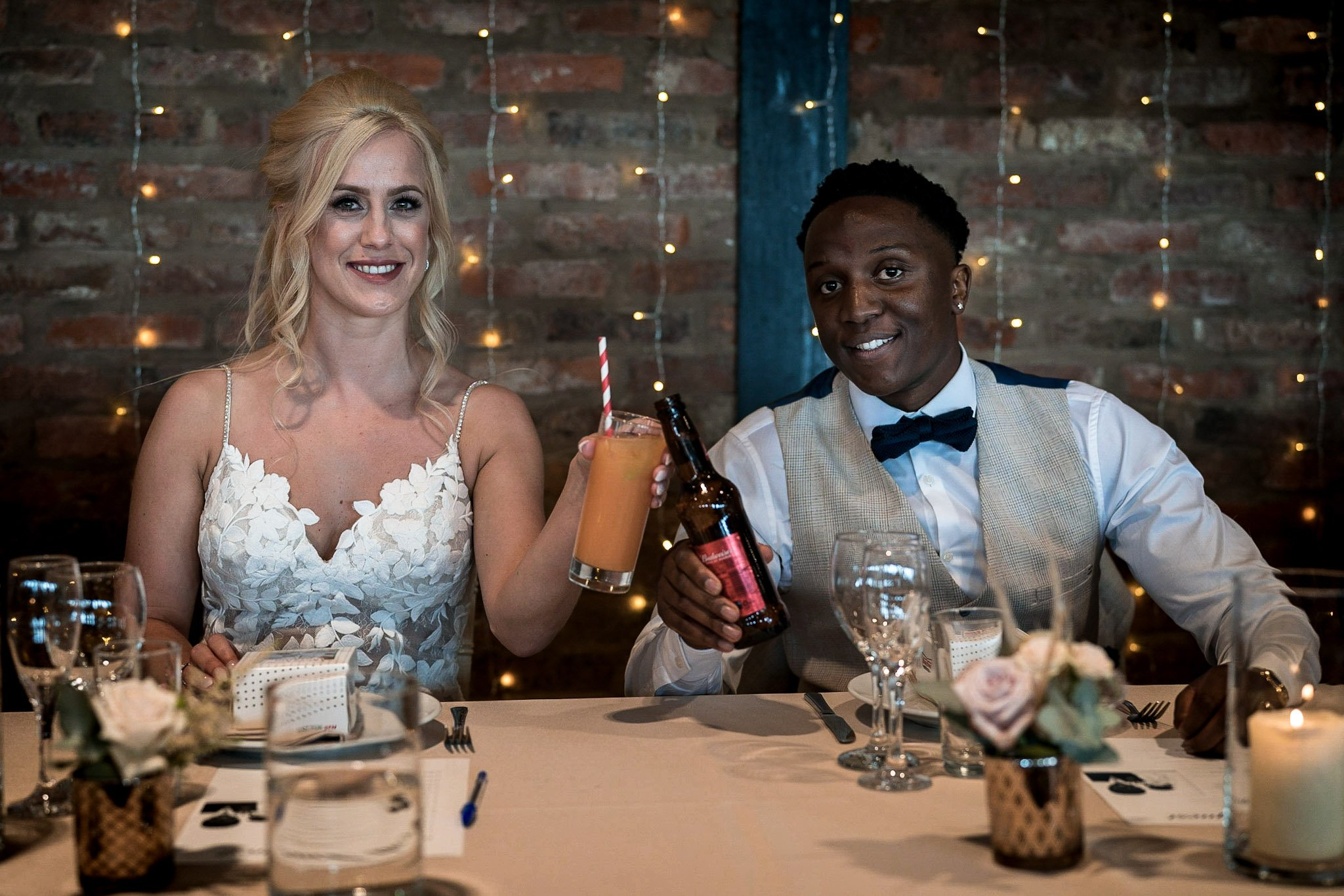 Your Favourite Frame YFFUK Mwasuku Norton Fields Atherstone bride and groom toasting with a beer and mango punch at the top table
