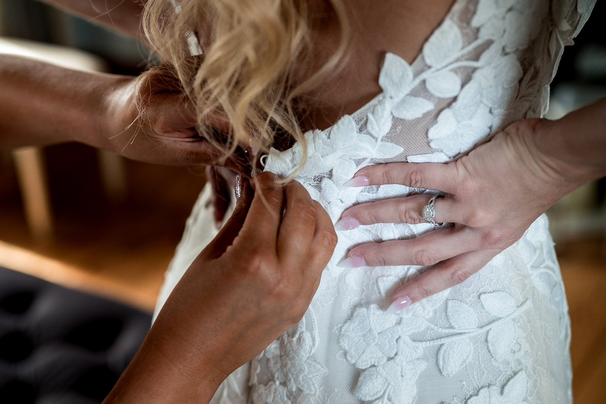 Your Favourite Frame YFFUK Mwasuku Norton Fields Atherstone bride being buttoned into her dress by her maid of honour engagement ring on her right hand