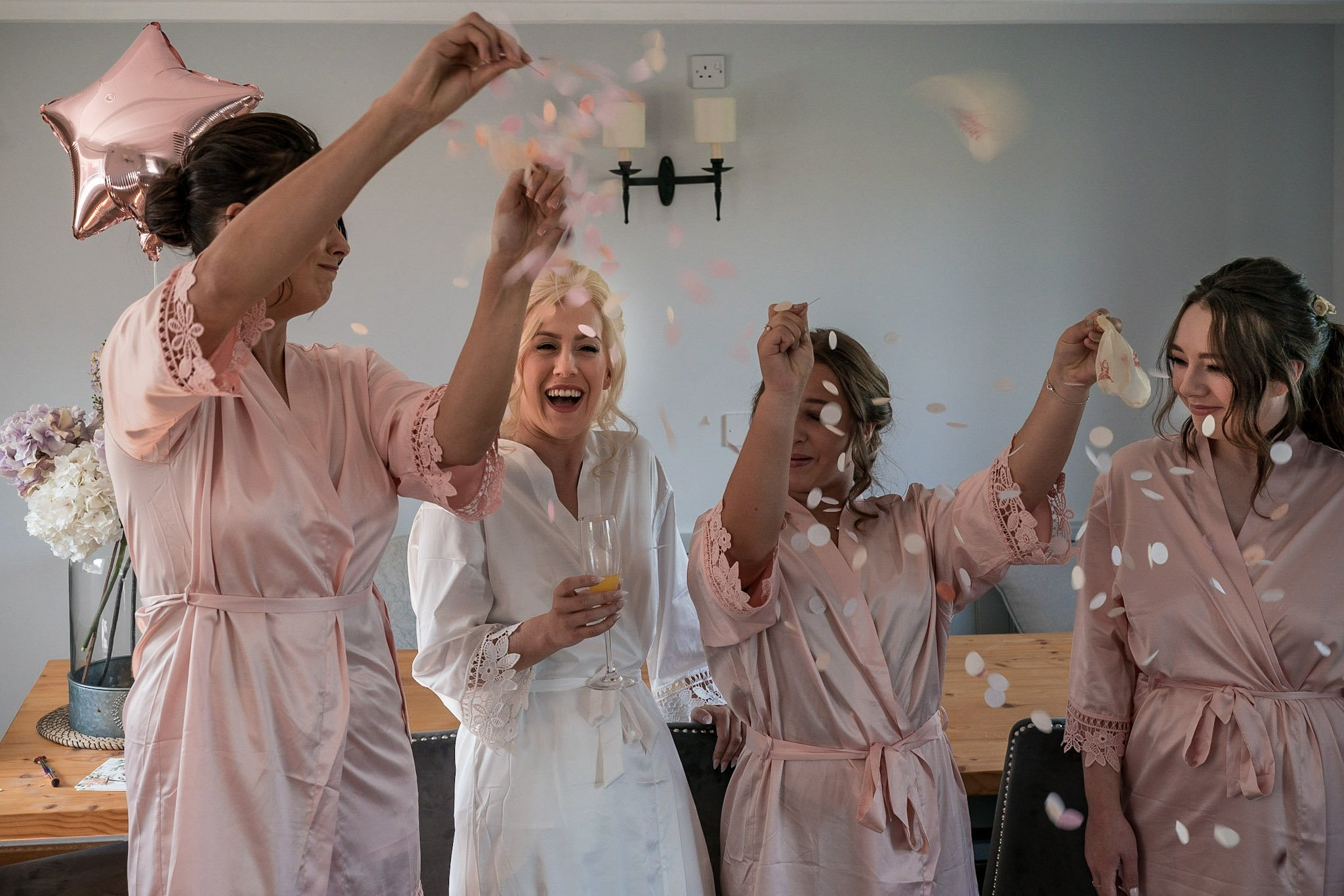 Your Favourite Frame YFFUK Mwasuku Norton Fields Atherstone bride being showered in confetti as her bridesmaids pop the balloons in the main cottage space
