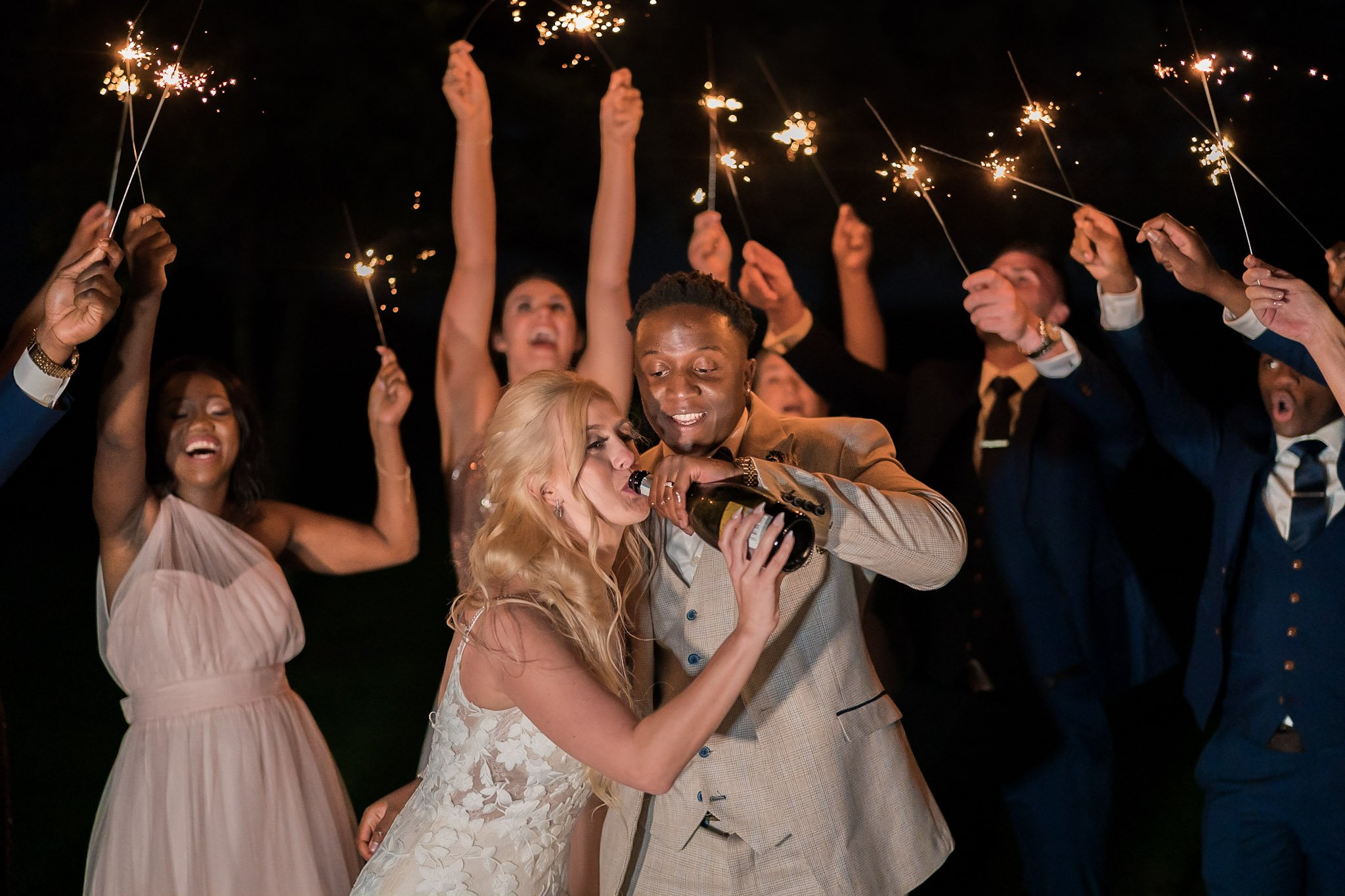 Your Favourite Frame YFFUK Mwasuku Norton Fields Atherstone bride drinking from the champagne bottle with her groom holding the bottle sparklers behind and above them