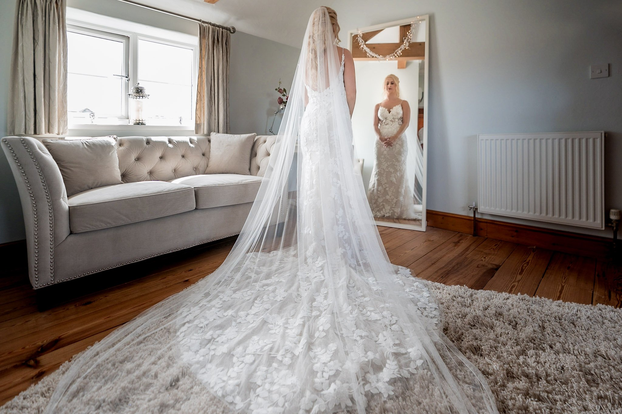 Your Favourite Frame YFFUK Mwasuku Norton Fields Atherstone bride in the bridal suite looking into the mirror with her dress and veil showing all the details on the back