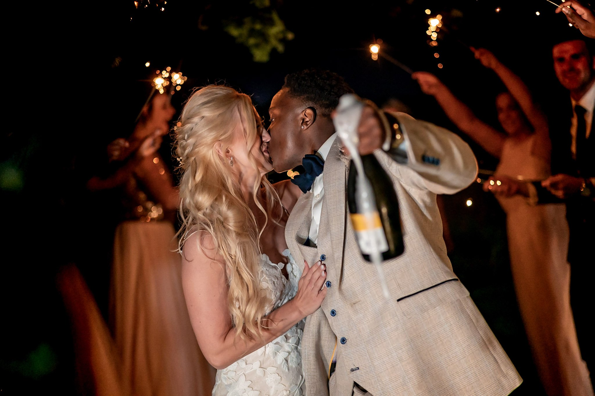 Your Favourite Frame YFFUK Mwasuku Norton Fields Atherstone bride kissing her groom while champagne spills out the bottle he is holding sparklers behind