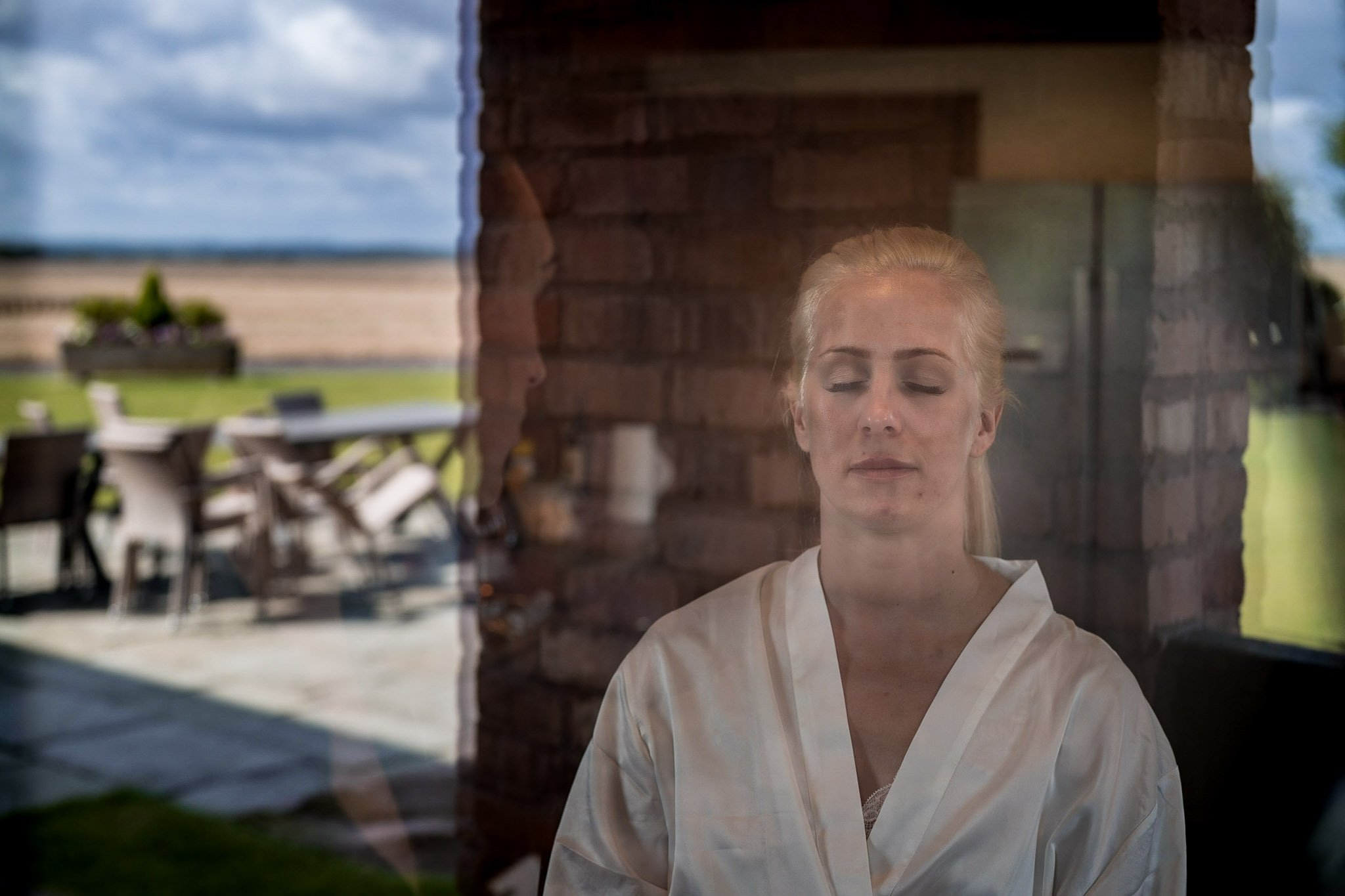 Your Favourite Frame YFFUK Mwasuku Norton Fields Atherstone brides having her makeup done with a reflection of the outside areas in the glass door