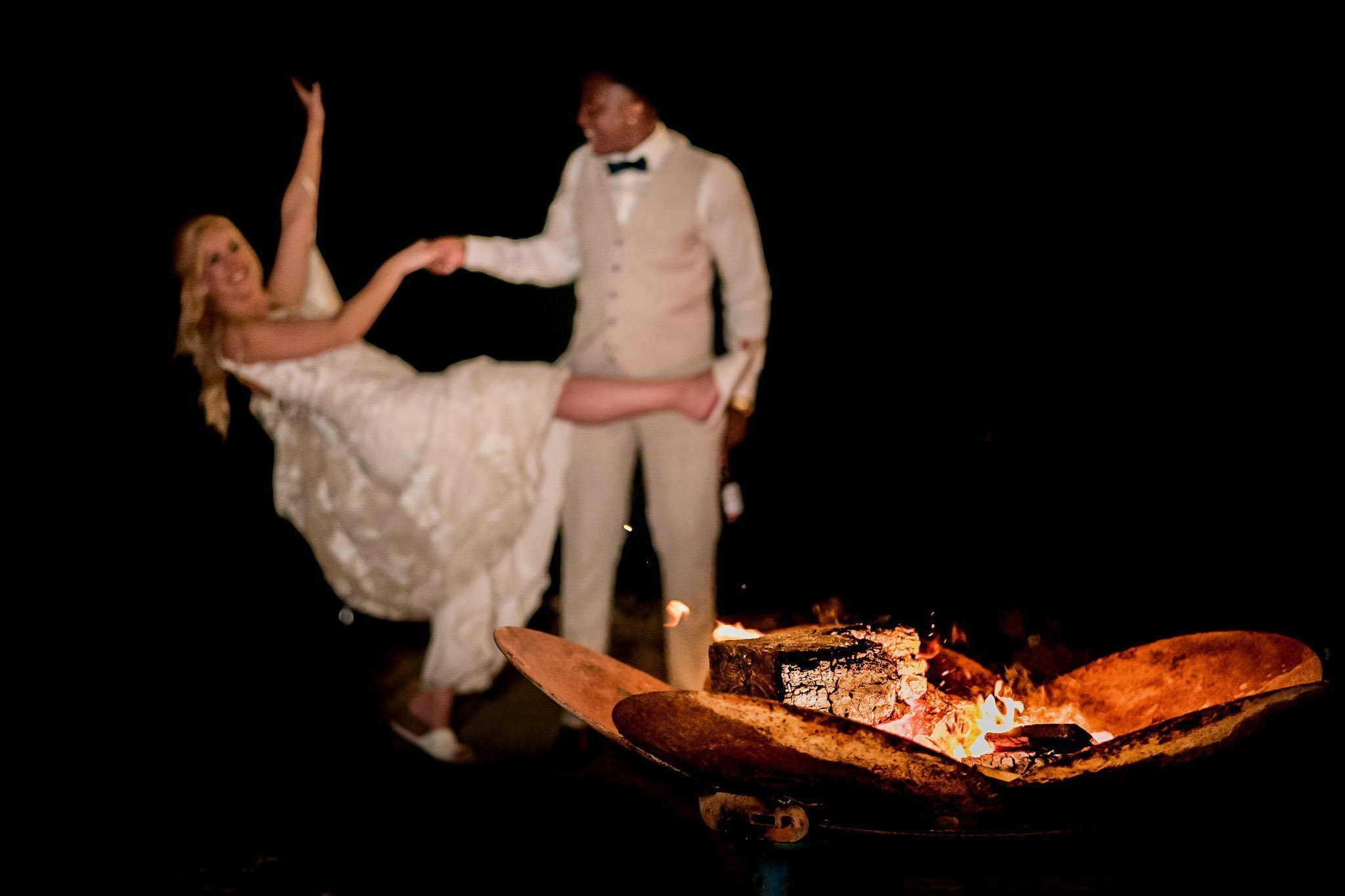 Your Favourite Frame YFFUK Mwasuku Norton Fields Atherstone groom holding his brides hand as she swoops down in front of the fire pits