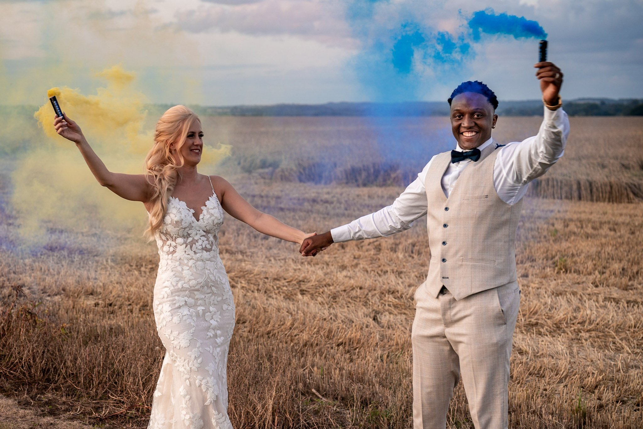 Your Favourite Frame YFFUK Mwasuku Norton Fields Atherstone sunset in front of the wheat fields blue skies groom and bride leaning close yellow and blue smoke effects