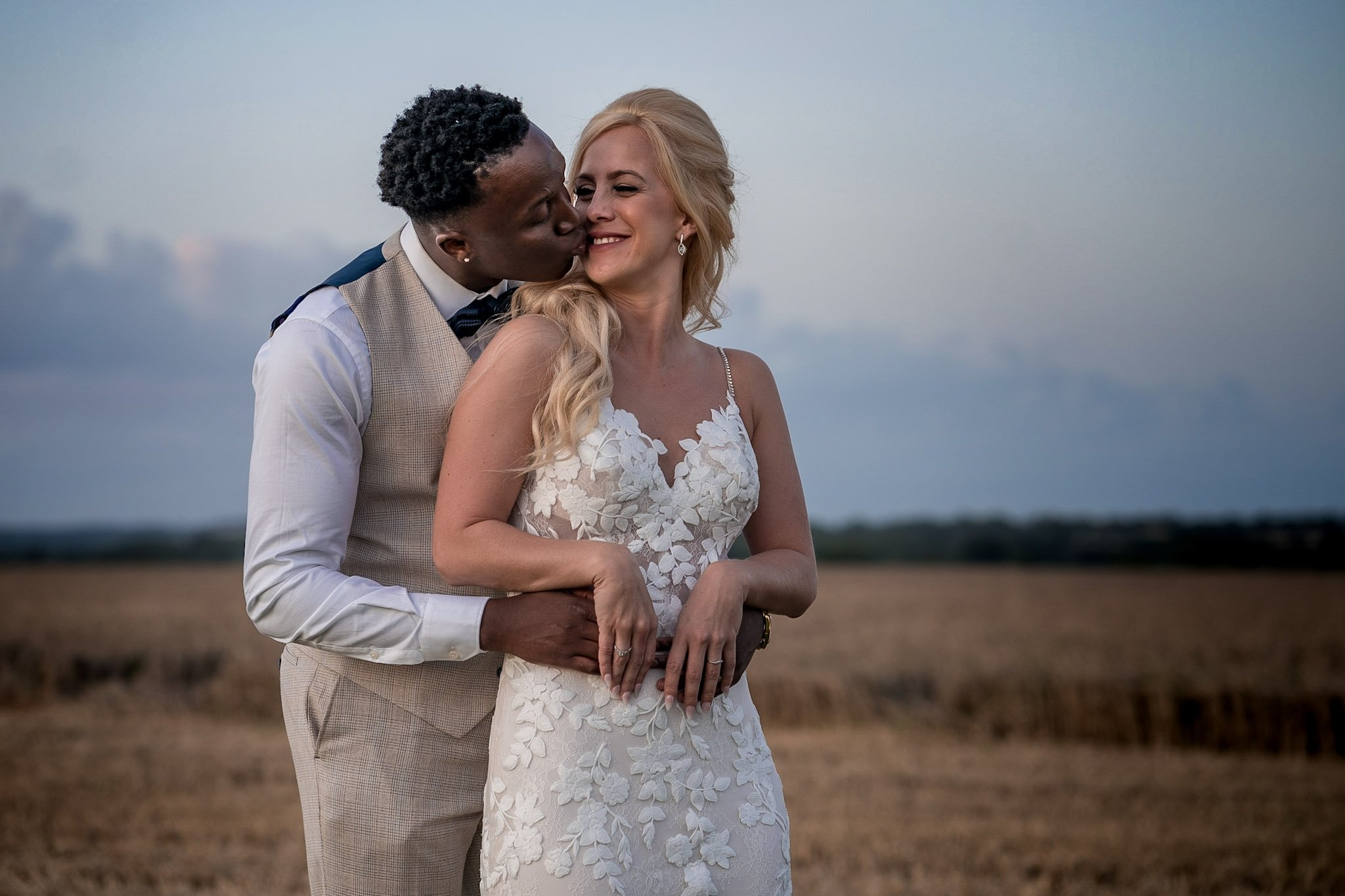 Your Favourite Frame YFFUK Mwasuku Norton Fields Atherstone sunset in front of the wheat fields blue sky and green horizon cuddles and kisses on a wedding day