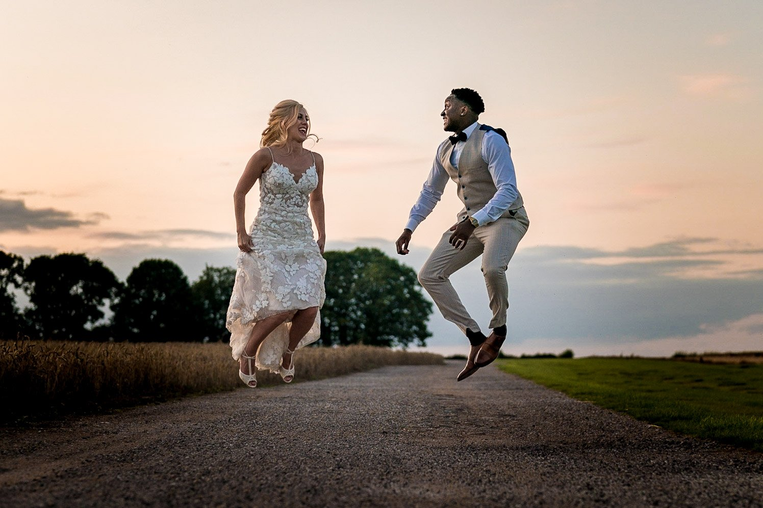 Your Favourite Frame YFFUK Mwasuku Norton Fields Atherstone sunset in front of the wheat fields golden skies and jumping for joy on their wedding day nothing but smiles and happiness