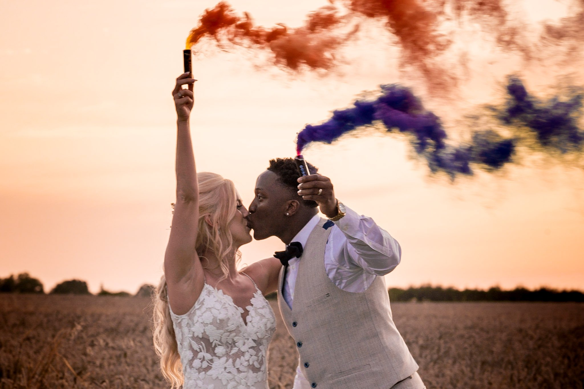 Your Favourite Frame YFFUK Mwasuku Norton Fields Atherstone sunset in front of the wheat fields golden skies groom and bride leaning close purple and orange smoke effects