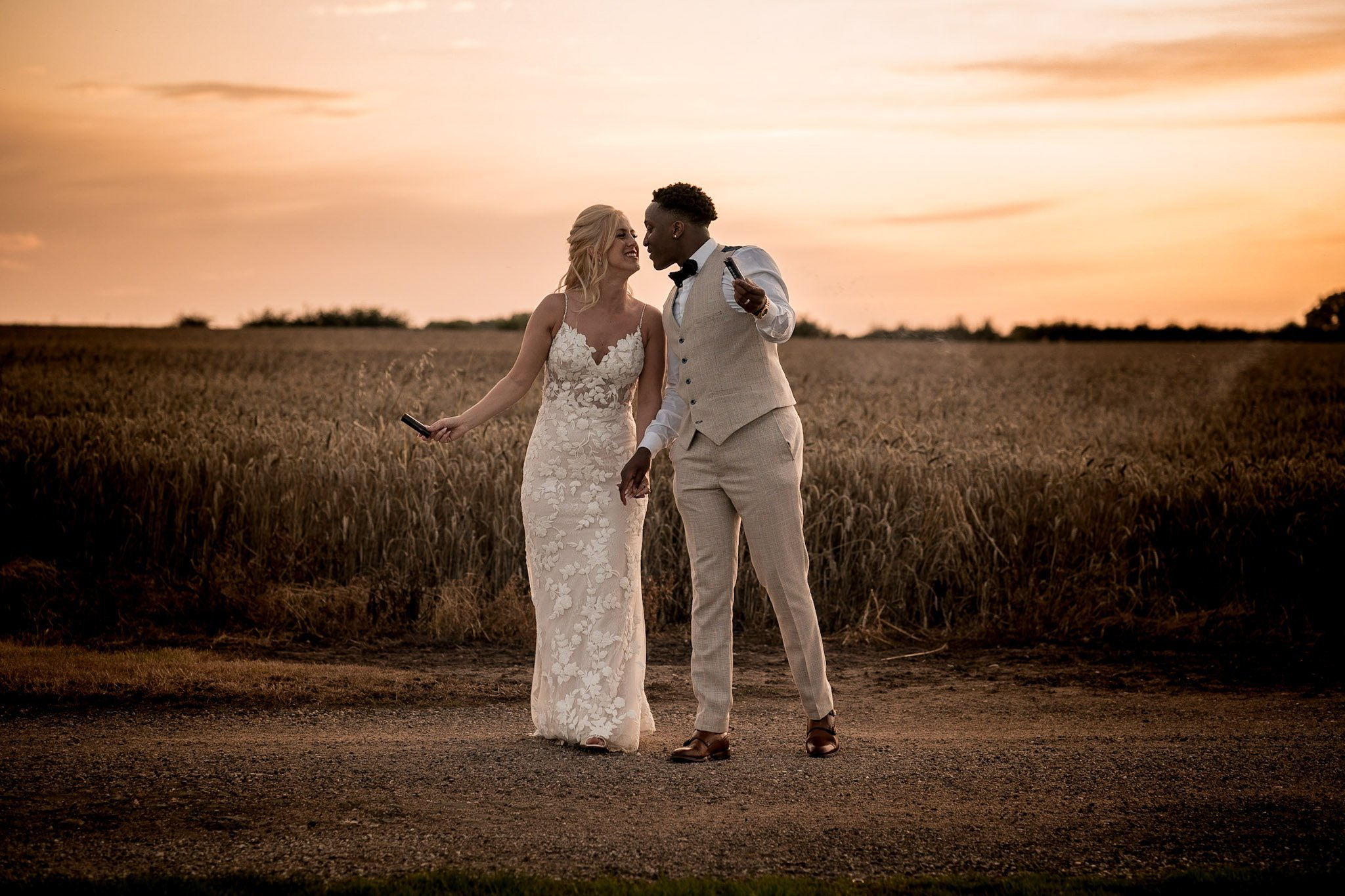 Your Favourite Frame YFFUK Mwasuku Norton Fields Atherstone sunset in front of the wheat fields golden skies groom and bride leaning close