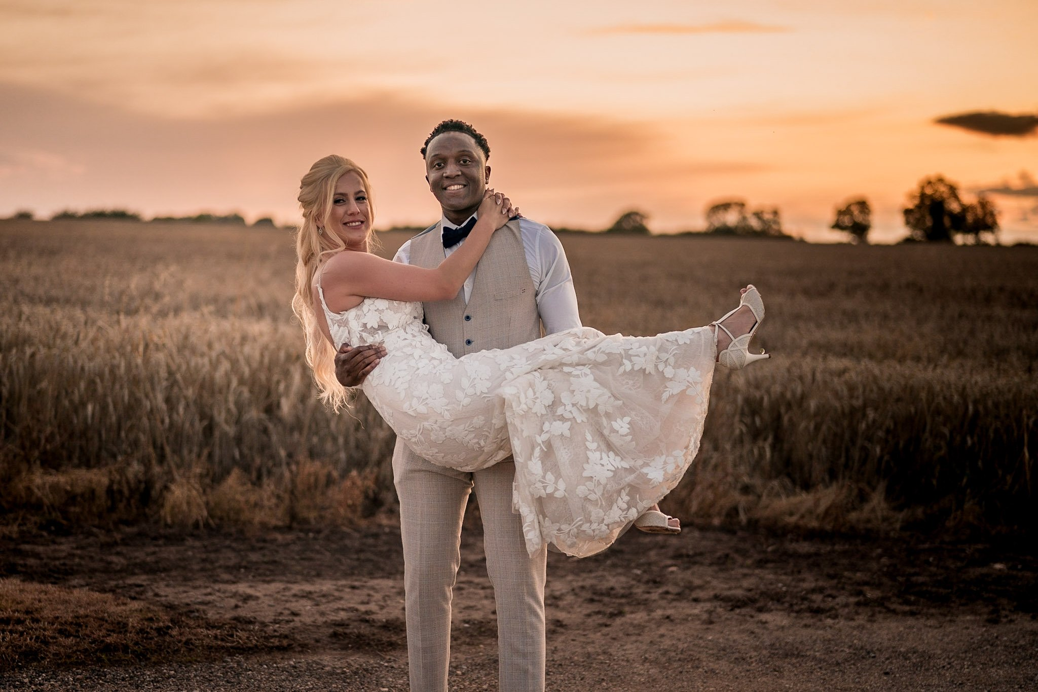 Your Favourite Frame YFFUK Mwasuku Norton Fields Atherstone sunset in front of the wheat fields golden skies groom holding his bride in his arms both smiling joy evident across their faces