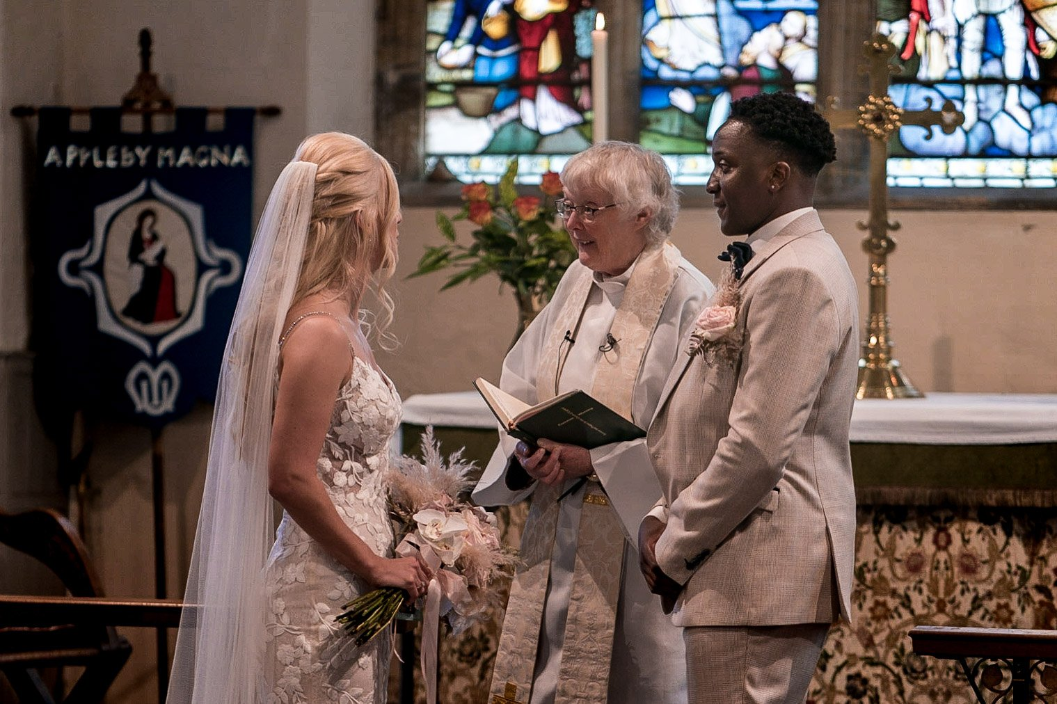Your Favourite Frame YFFUK Mwasuku St Michaels Church Appleby Magna bride and groom at the high altar for their wedding blessing with the vicar smiling through the middle groom beaming