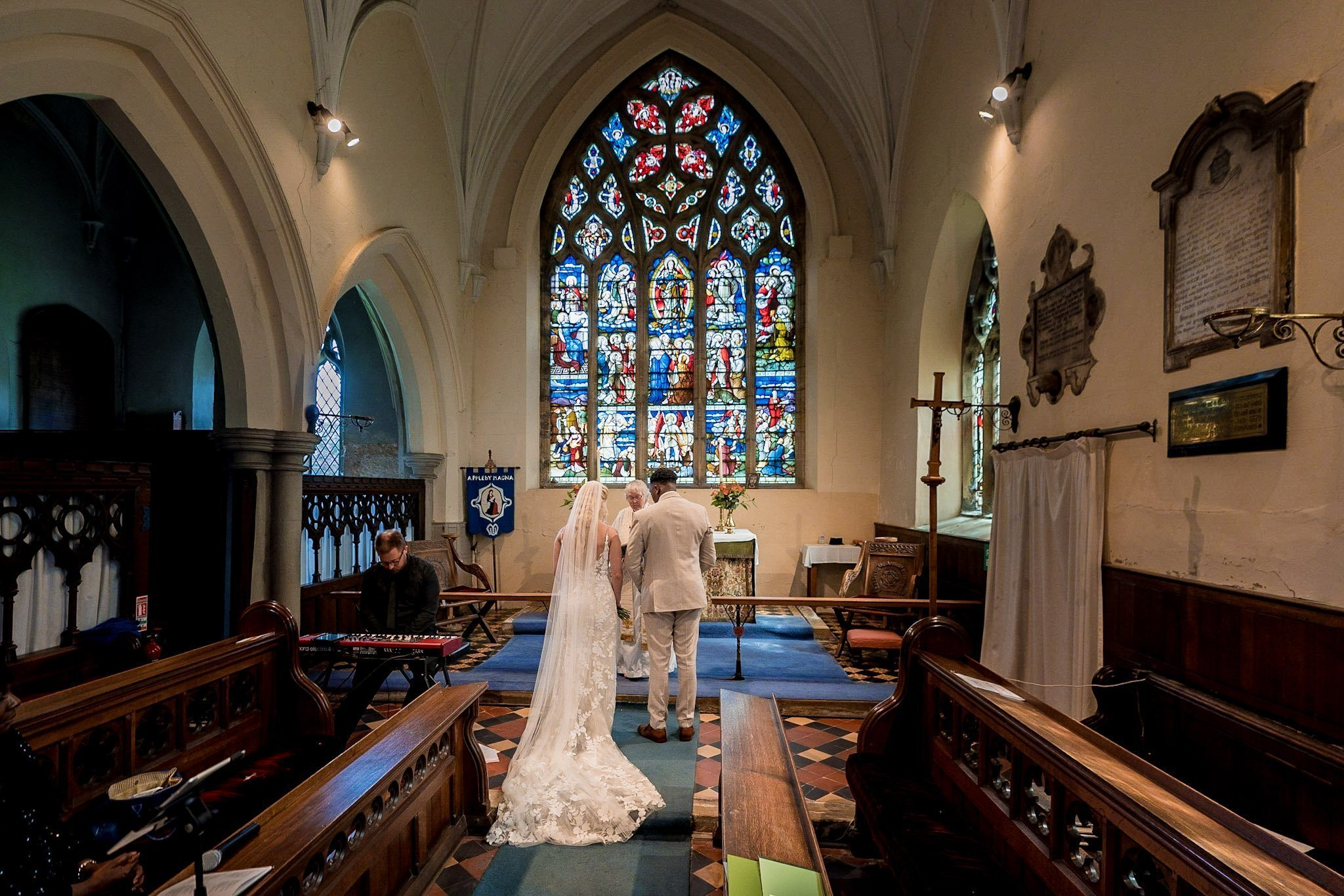 Your Favourite Frame YFFUK Mwasuku St Michaels Church Appleby Magna bride and groom at the high altar for their wedding blessing with the vicar smiling through the middle