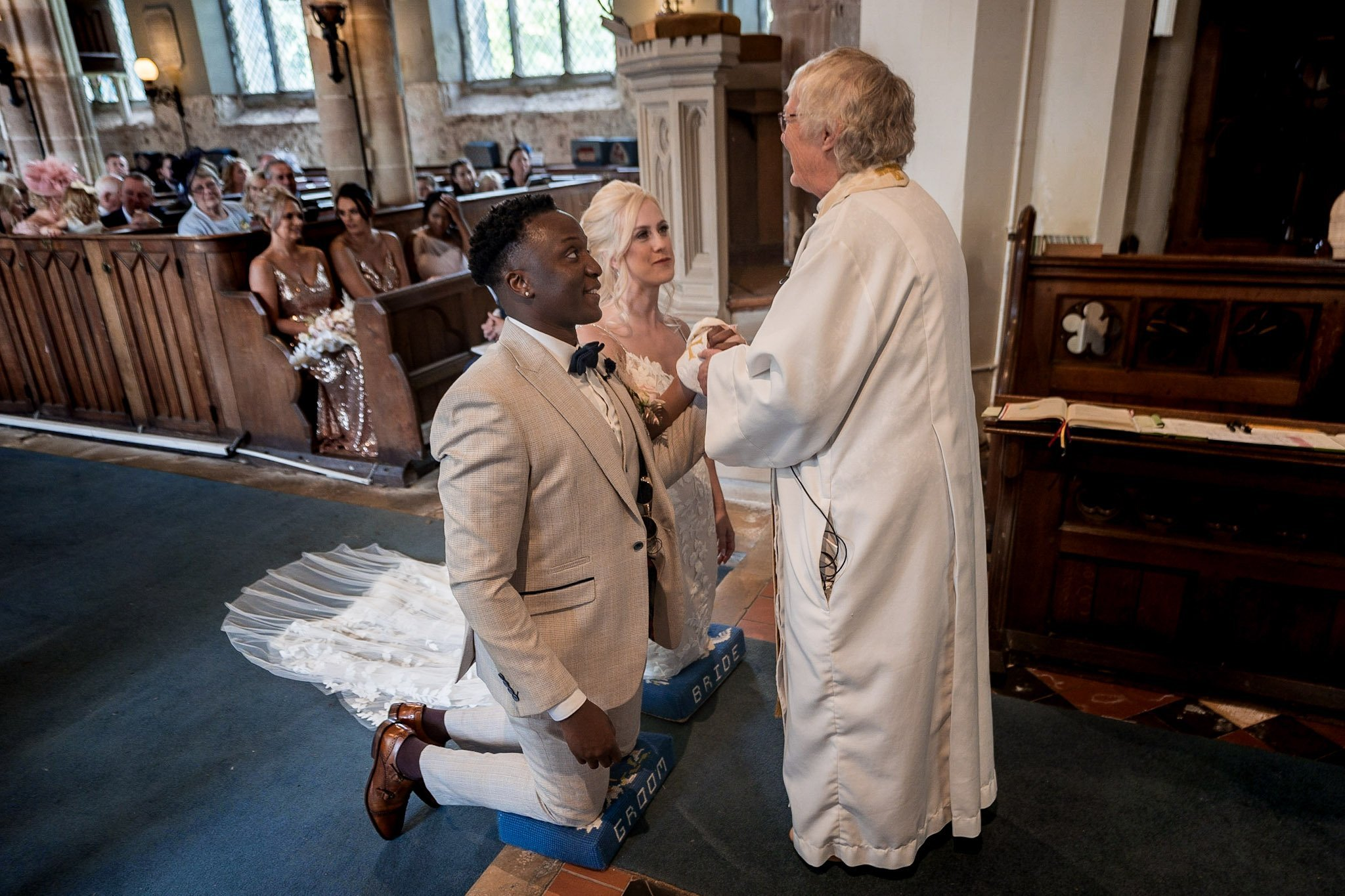 Your Favourite Frame YFFUK Mwasuku St Michaels Church Appleby Magna bride and groom kneeling at the foot of the altar receiving their wedding blessing from the vicar