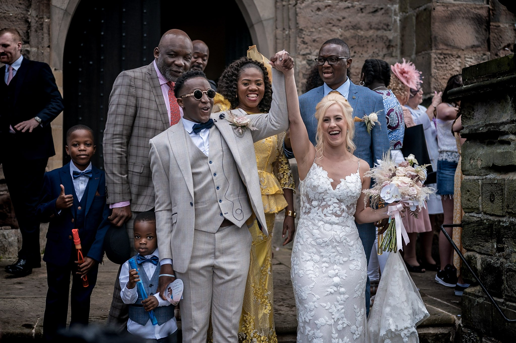 Your Favourite Frame YFFUK Mwasuku St Michaels Church Appleby Magna bride and groom on the front steps of the church arms aloft in celebration
