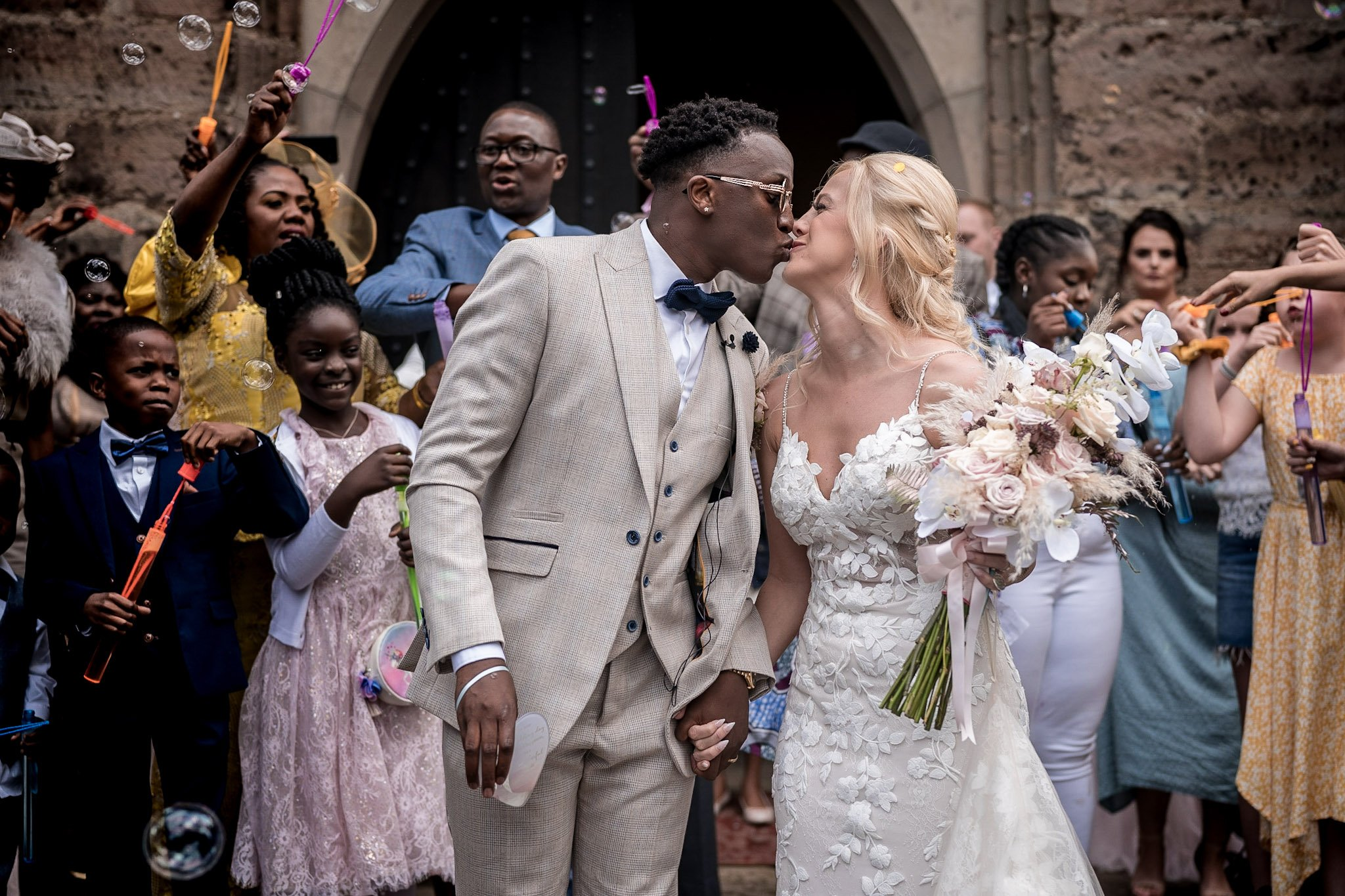 Your Favourite Frame YFFUK Mwasuku St Michaels Church Appleby Magna bride and groom on the front steps of the church getting bubbles blown over them with some confetti as well