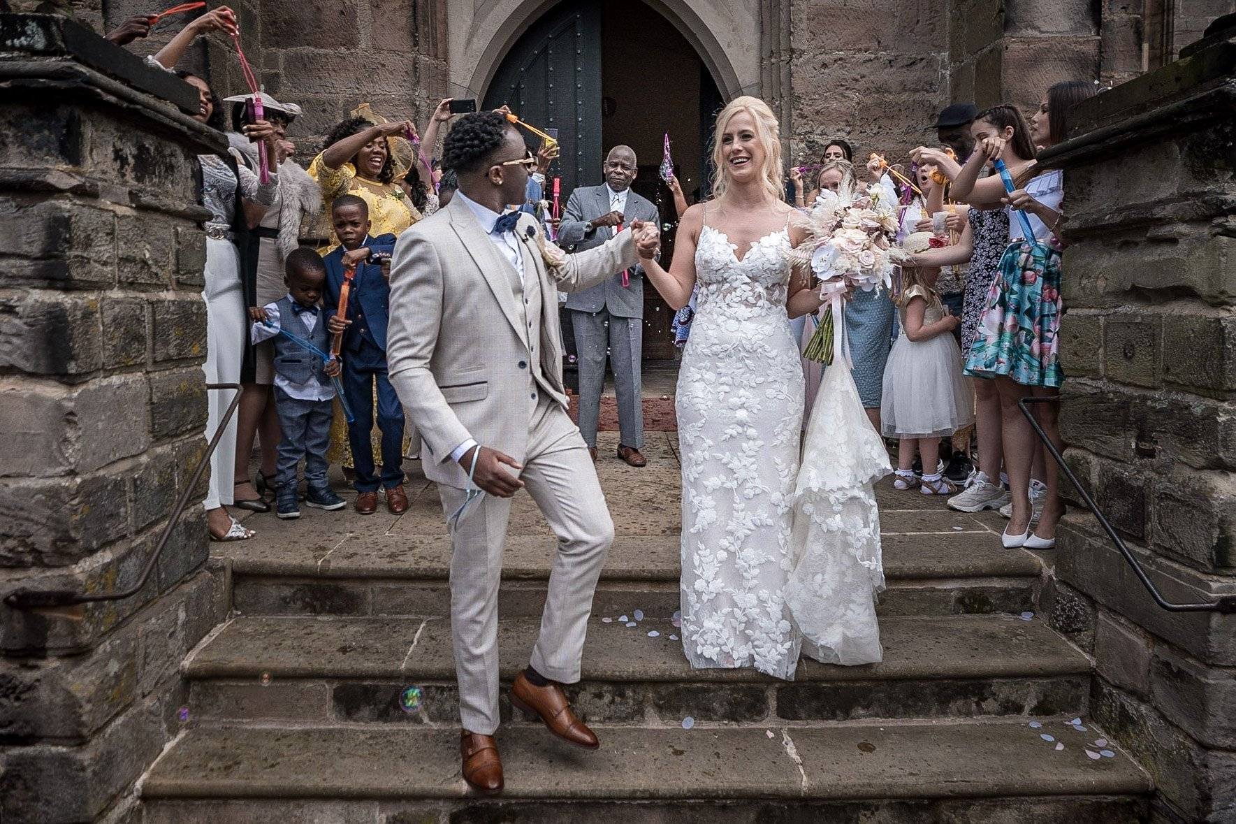 Your Favourite Frame YFFUK Mwasuku St Michaels Church Appleby Magna bride and groom on the front steps of the church getting bubbles blown over them