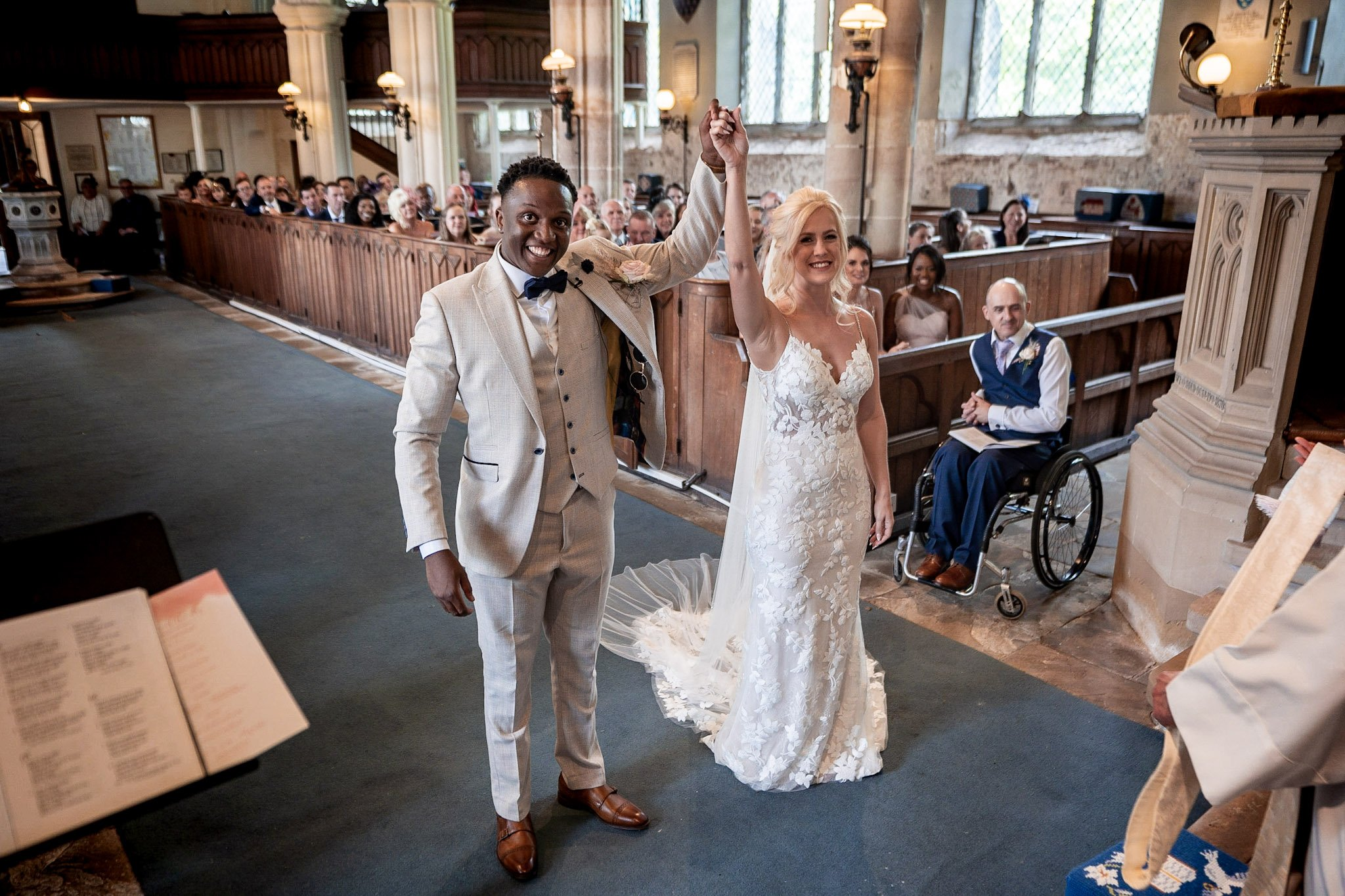 Your Favourite Frame YFFUK Mwasuku St Michaels Church Appleby Magna bride and groom raising their hands held together in the air to salute their guests and their vows standard view from the choral pews