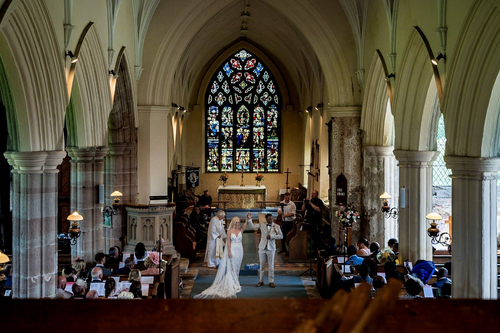 Your Favourite Frame YFFUK Mwasuku St Michaels Church Appleby Magna bride and groom raising their hands held together in the air to salute their guests and their vows top down view from the balcony