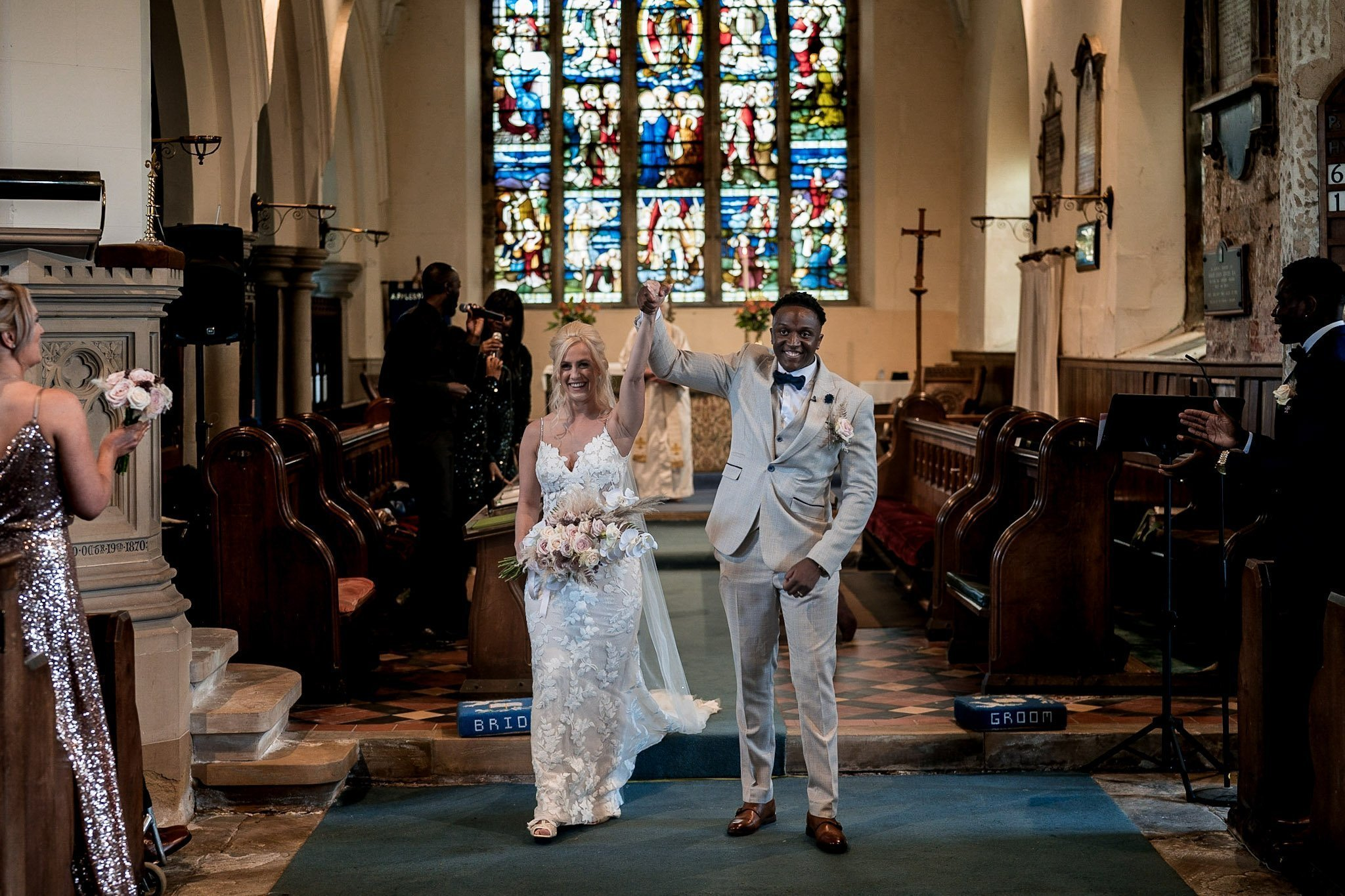 Your Favourite Frame YFFUK Mwasuku St Michaels Church Appleby Magna bride and groom walking back down the aisle together after their vows arms aloft in celebration floor view