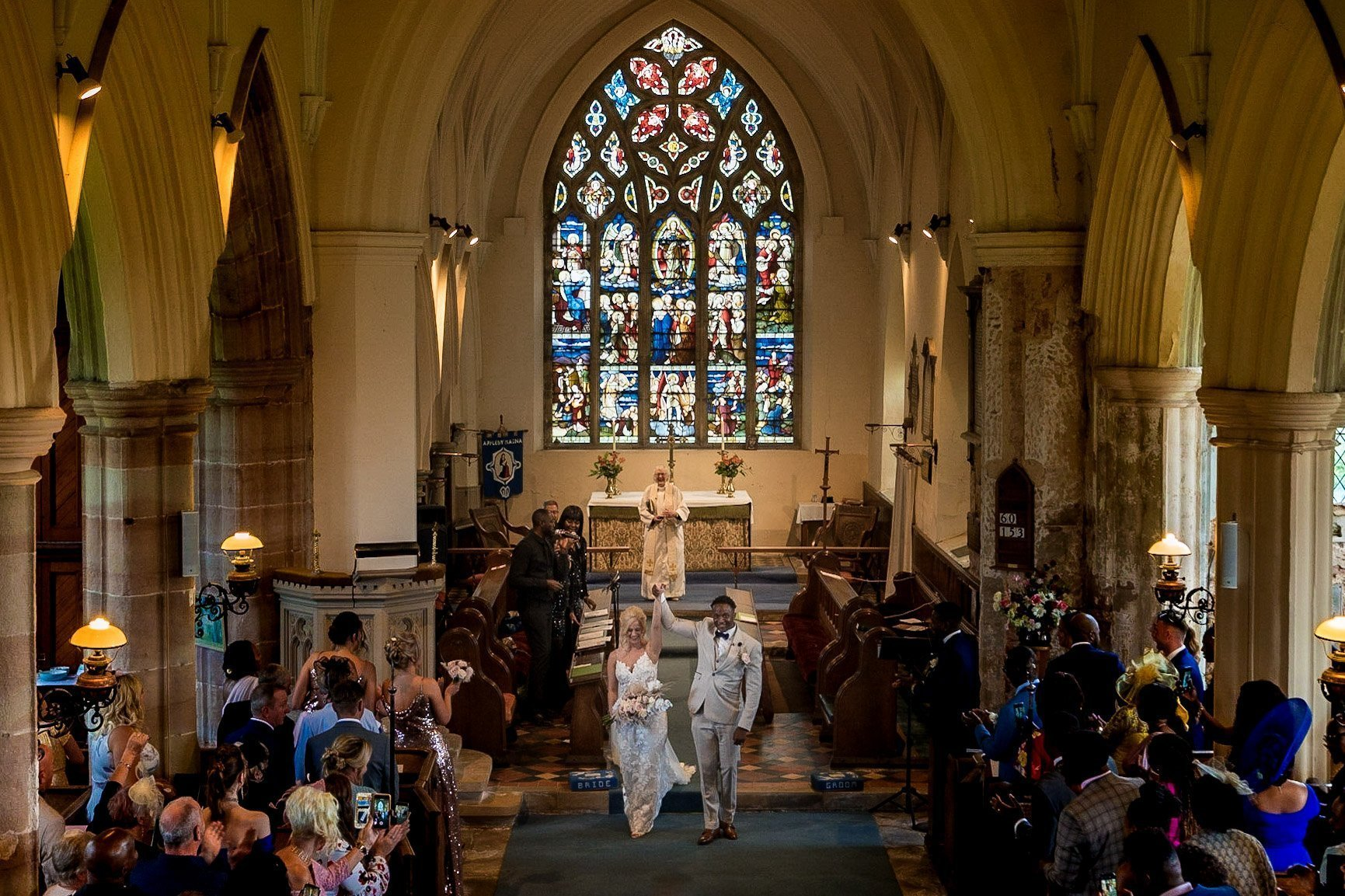 Your Favourite Frame YFFUK Mwasuku St Michaels Church Appleby Magna bride and groom walking back down the aisle together after their vows arms aloft in celebration