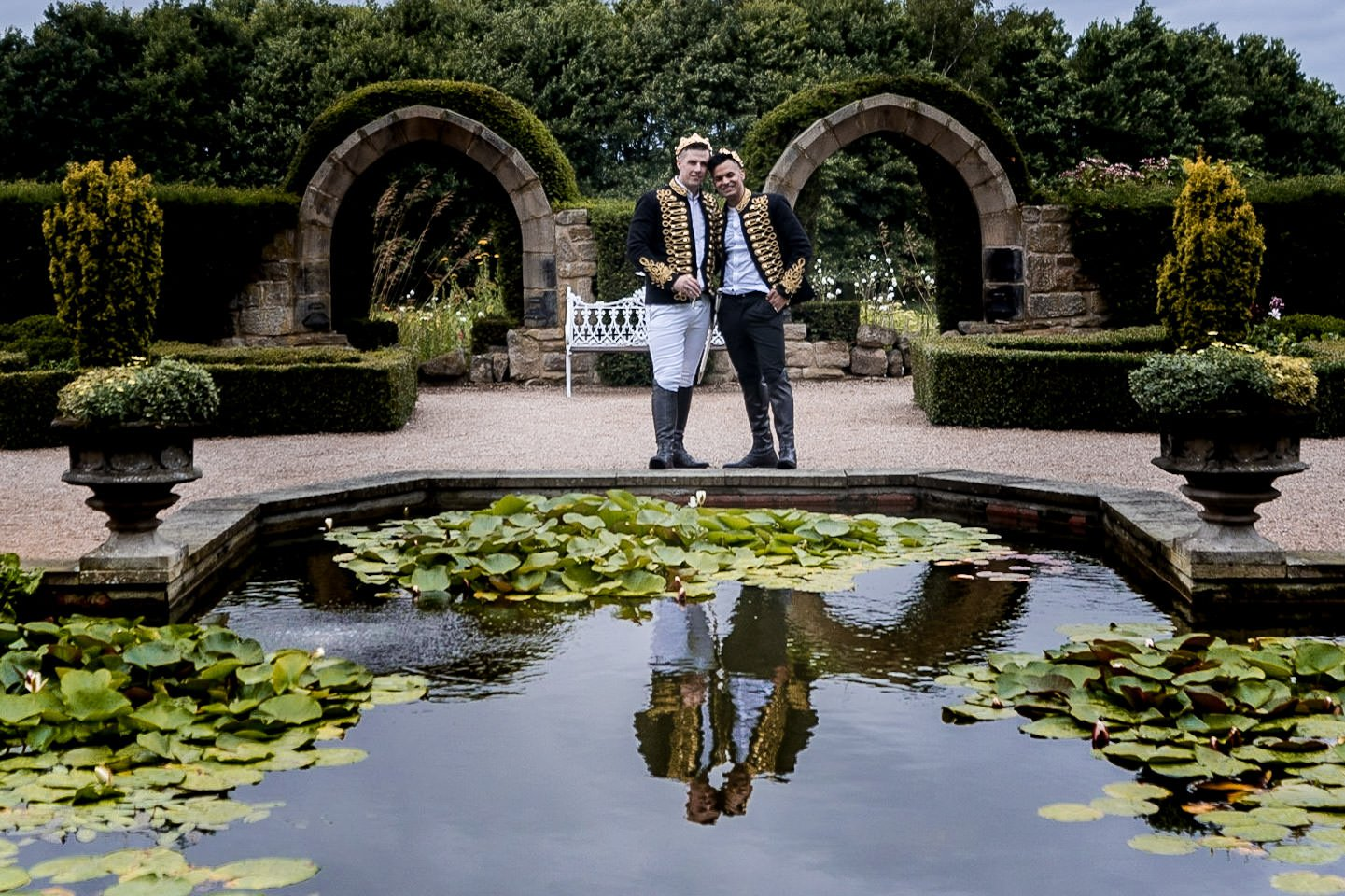 Allerton Castle Knaresborough Hutchinson Weddings Photography Groom and groom by the edge of the reflecting pool in the memorial garden