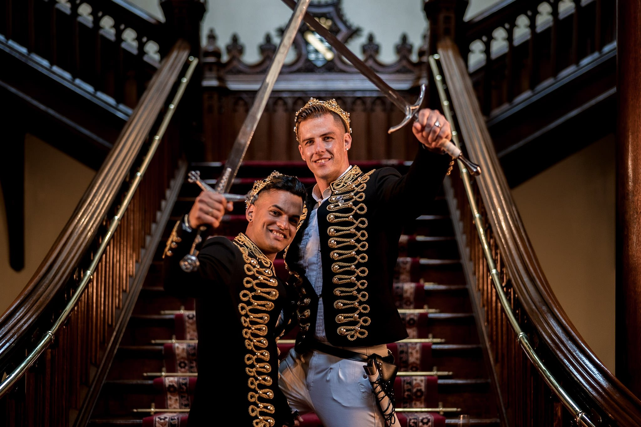 Allerton Castle Knaresborough Hutchinson Weddings Photography groom and groom on the grand staircase holding their swords aloft and crossing them