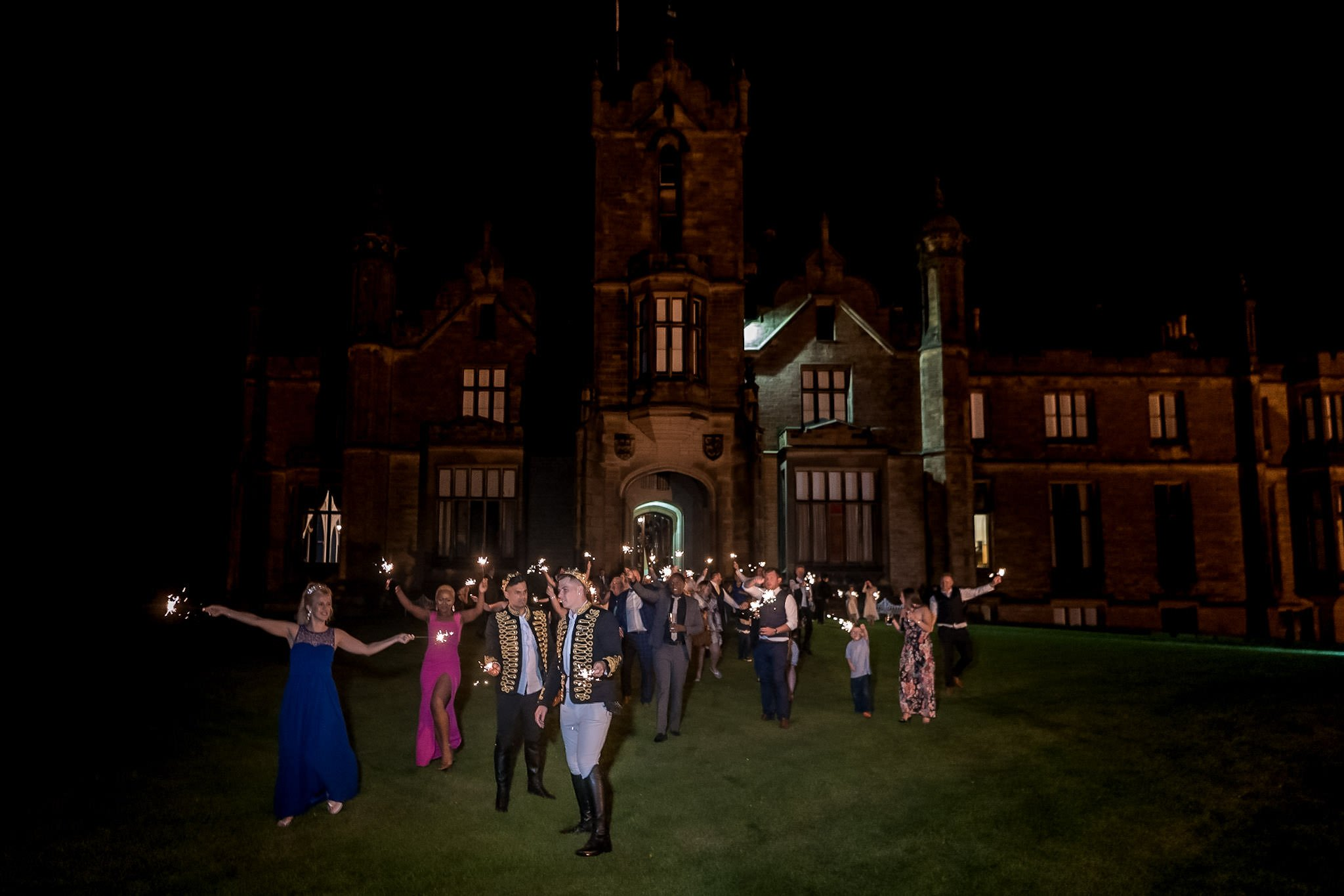 Allerton Castle Knaresborough Hutchinson Weddings Photography groom and groom playing on the front lawn with sparklers castle behind night lit