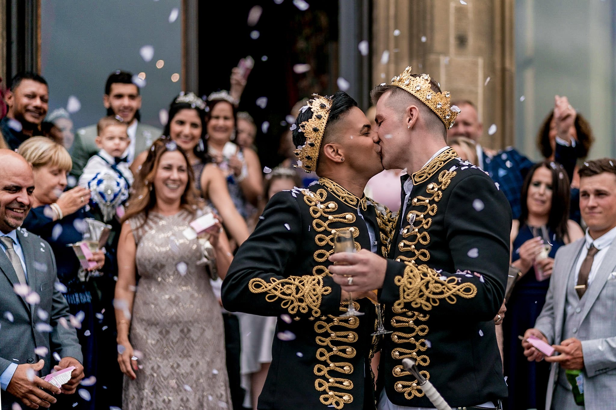 Allerton Castle Knaresborough Hutchinson Weddings Photography groom and husband kissing while being showered with confetti by their guests on the rear patio