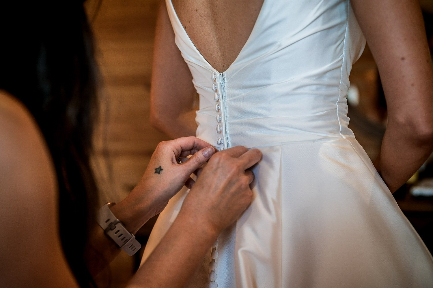 Foxton Lock Lodges Lockwood Weddings Photography Bride being buttoned into her wedding dress by her maid of honour